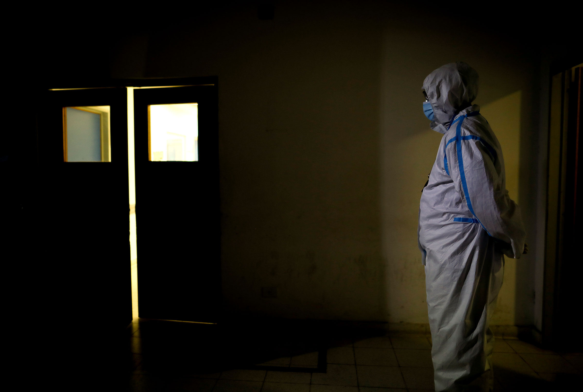 A healthcare worker stands outside Llavallol Dr. Norberto Raúl Piacentini Hospital in Lomas de Zamora, Argentina, Saturday, May 1, 2021. The latest outbreak of coronavirus cases has filled clinics in Buenos Aires and nearby towns with patients.