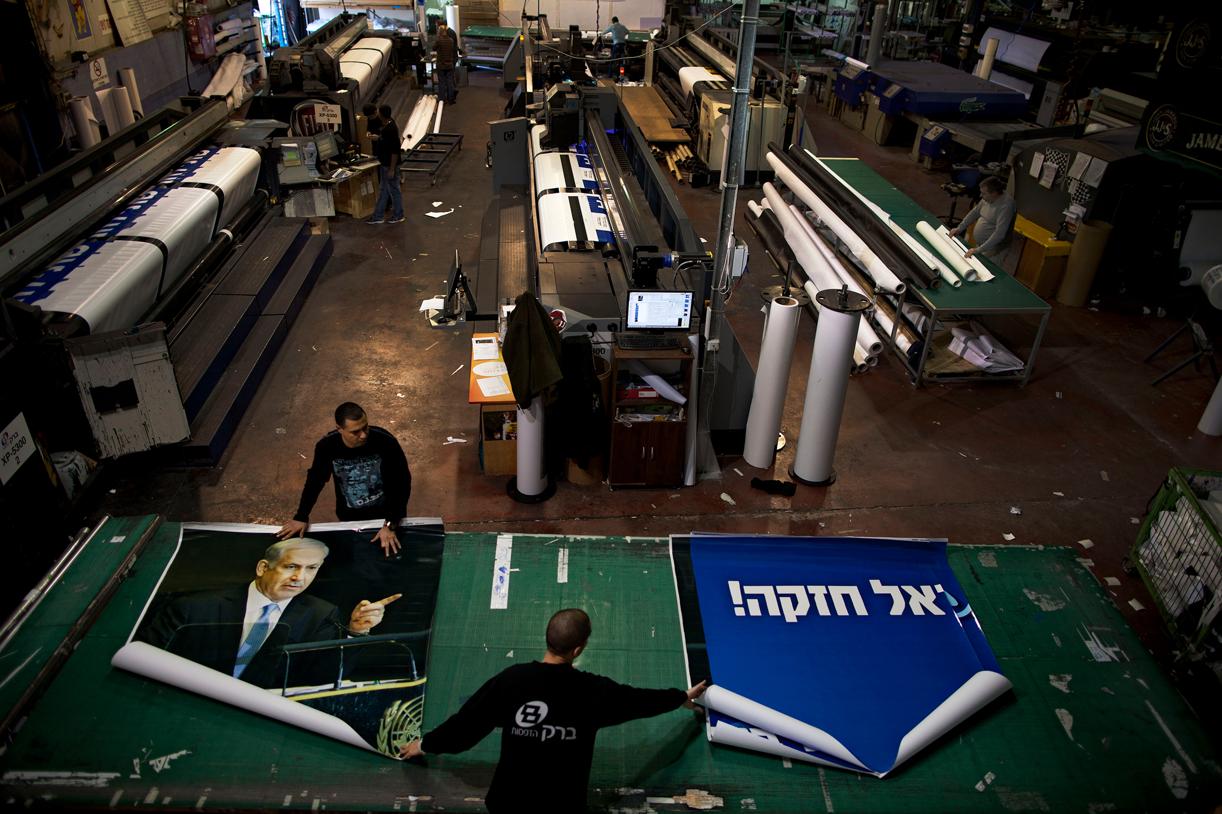 Printing house employees work on a campaign billboard for Israeli Prime Minister and Likud Party leader Benjamin Netanyahu in central Petah Tikva in 2013.