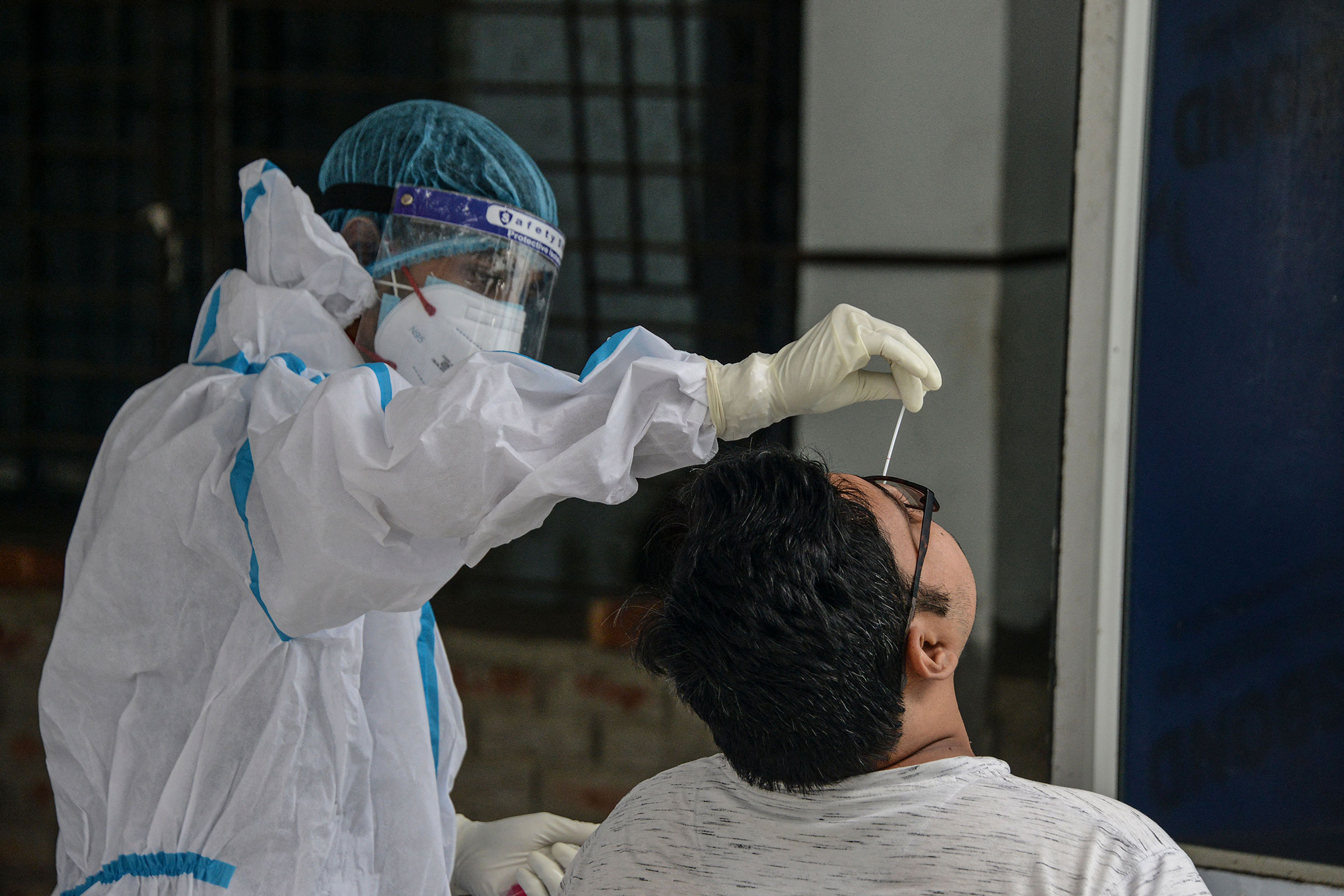A health worker collects a sample for a COVID-19 test at the North Bengal Medical college and hospital on the outskirts of Siliguri on June 8, 2021.