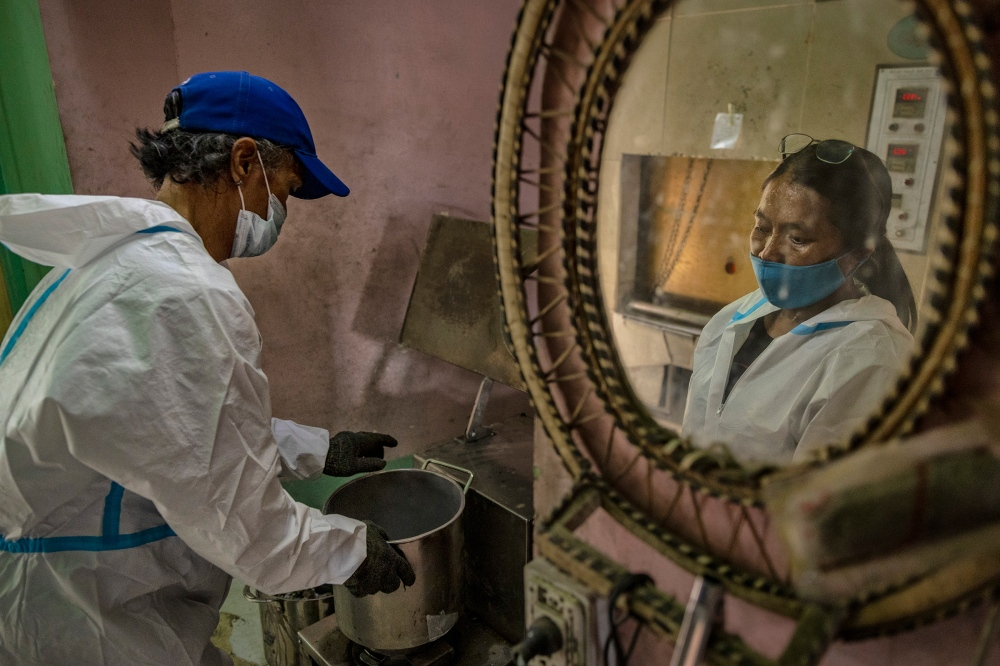 Cemetery workers grind the ashes of a COVID-19 victim at a public crematorium in Pasay, Metro Manila, on April 21.