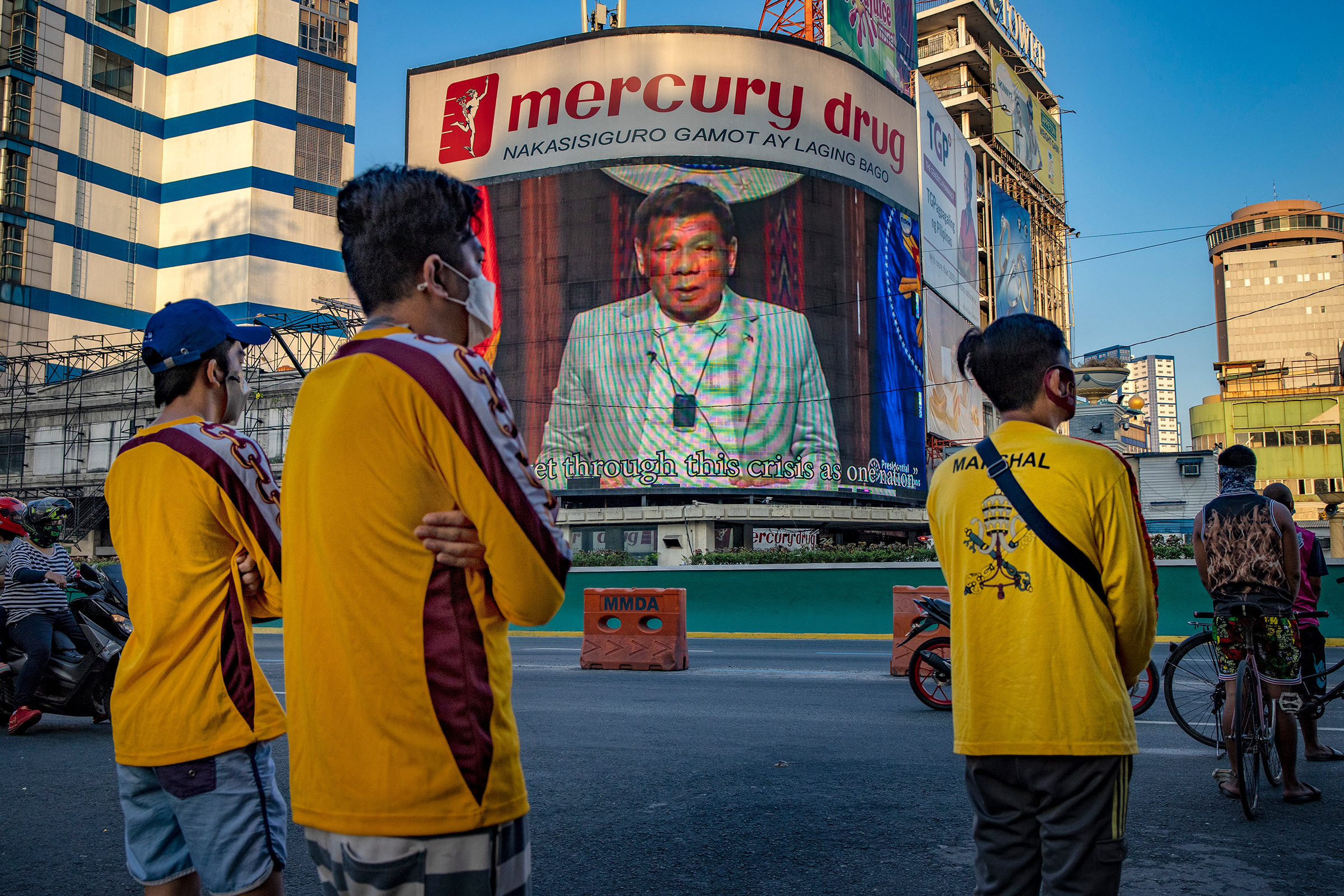 An electronic billboard displays a video of Duterte as Catholic devotees pray outside a closed church in Manila on April 2, defying government orders to avoid religious gatherings and stay home during Holy Week to curb the spread of the coronavirus.