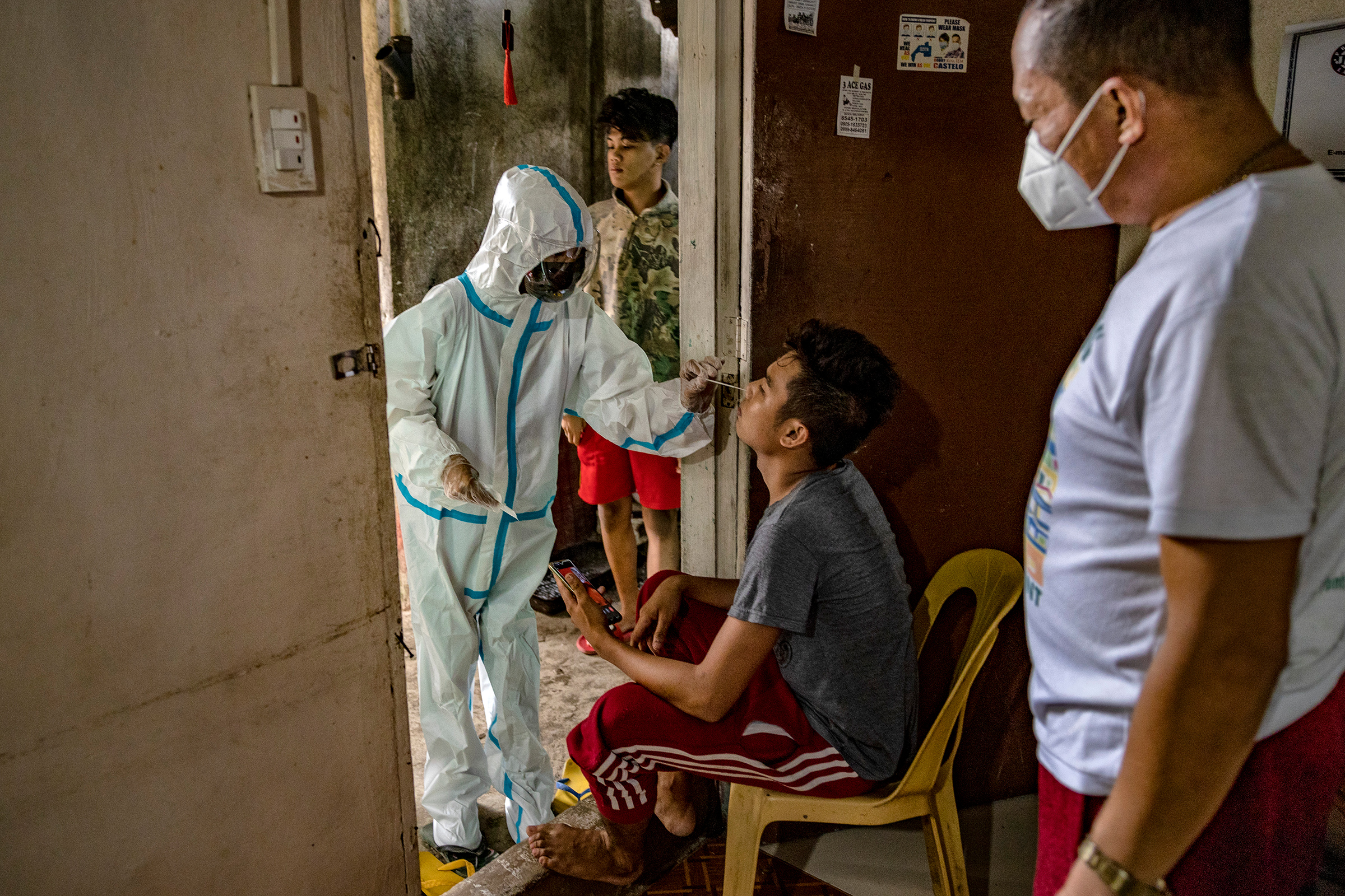 Katrina Pelotin, a field nurse from the City Epidemiology and Surveillance Unit, conducts a swab test on a family member of a COVID-19 patient isolating at home as part of contact tracing efforts in Quezon City, Metro Manila, on April 15.