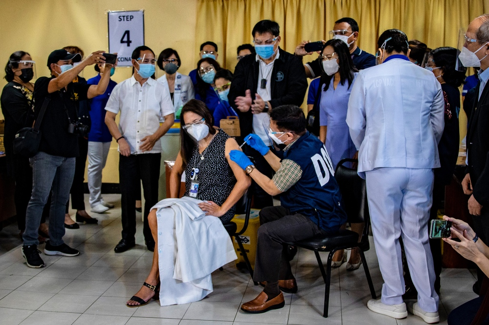 Health Secretary Francisco Duque III administers a shot of Sinovac Biotech's CoronaVac vaccine on a health care worker during the first day of COVID-19 vaccinations at the Lung Center of the Philippines Hospital in Quezon City on March 1.