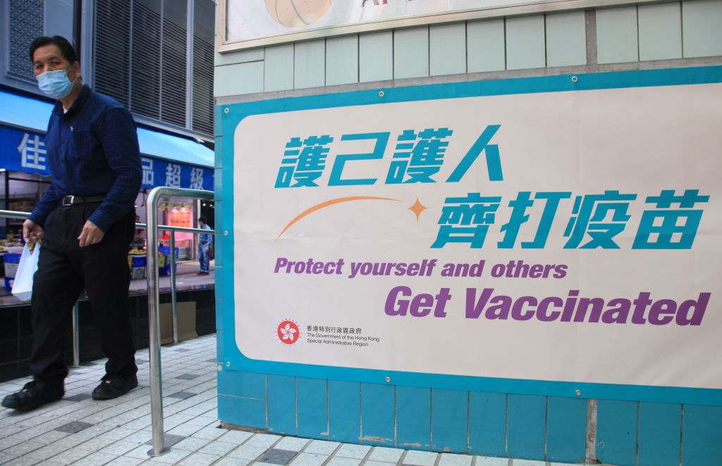 A man in a facemask walked past a COVID-19 vaccination center in Hong Kong on March 25, 2021. After a sluggish vaccination, more Hong Kong residents are finally signing up for their first shots in June.