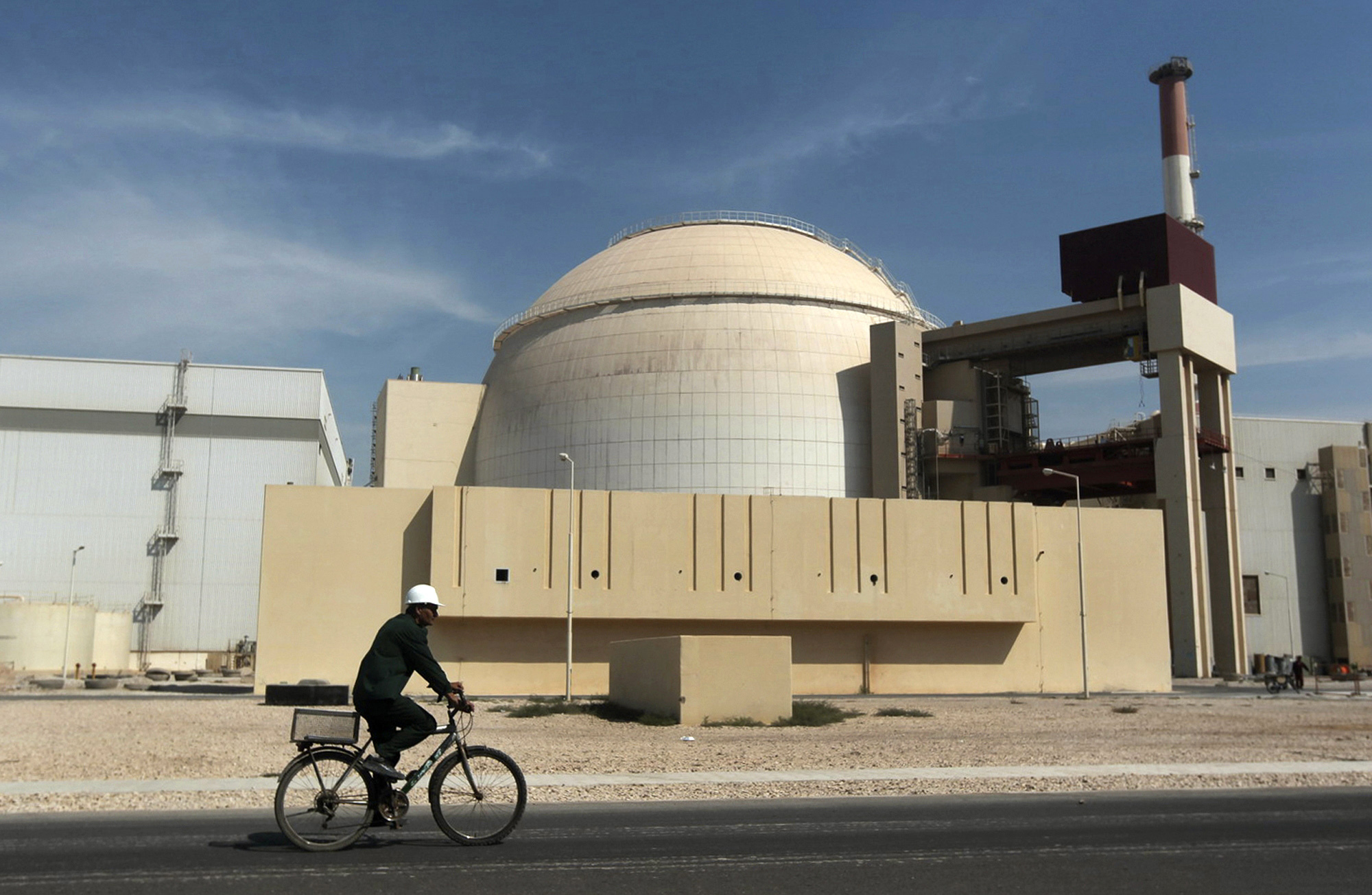 """In this Oct. 26, 2010 file photo, a worker rides a bicycle in front of the reactor building of the Bushehr nuclear power plant, just outside the southern city of Bushehr. Iran's sole nuclear power plant has undergone a temporary emergency shutdown, state TV reported on Sunday, June 20, 2021. An official from the state electric energy company, Gholamali Rakhshanimehr, said on a talk show that the Bushehr plant shutdown began on Saturday and would last  for three to four days."""""""