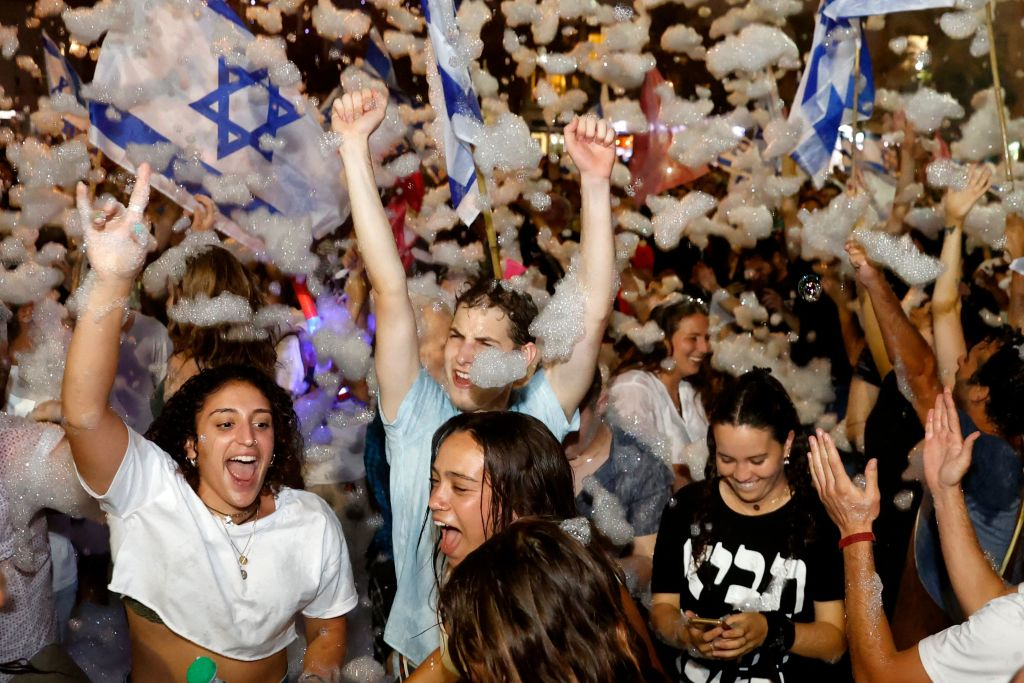 Israeli demonstrators celebrate the passing of a Knesset vote confirming a new coalition government during a rally in Tel Aviv on June 13, 2021.