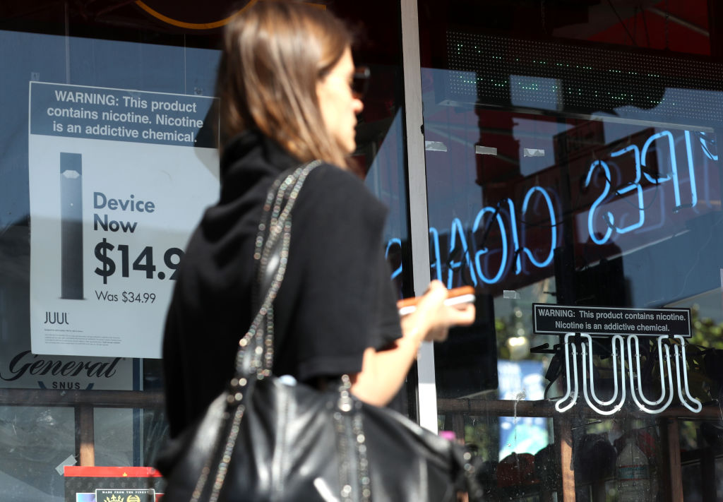 A pedestrian walks by a window advertisement for Juul products in San Francisco on Oct. 17, 2019.