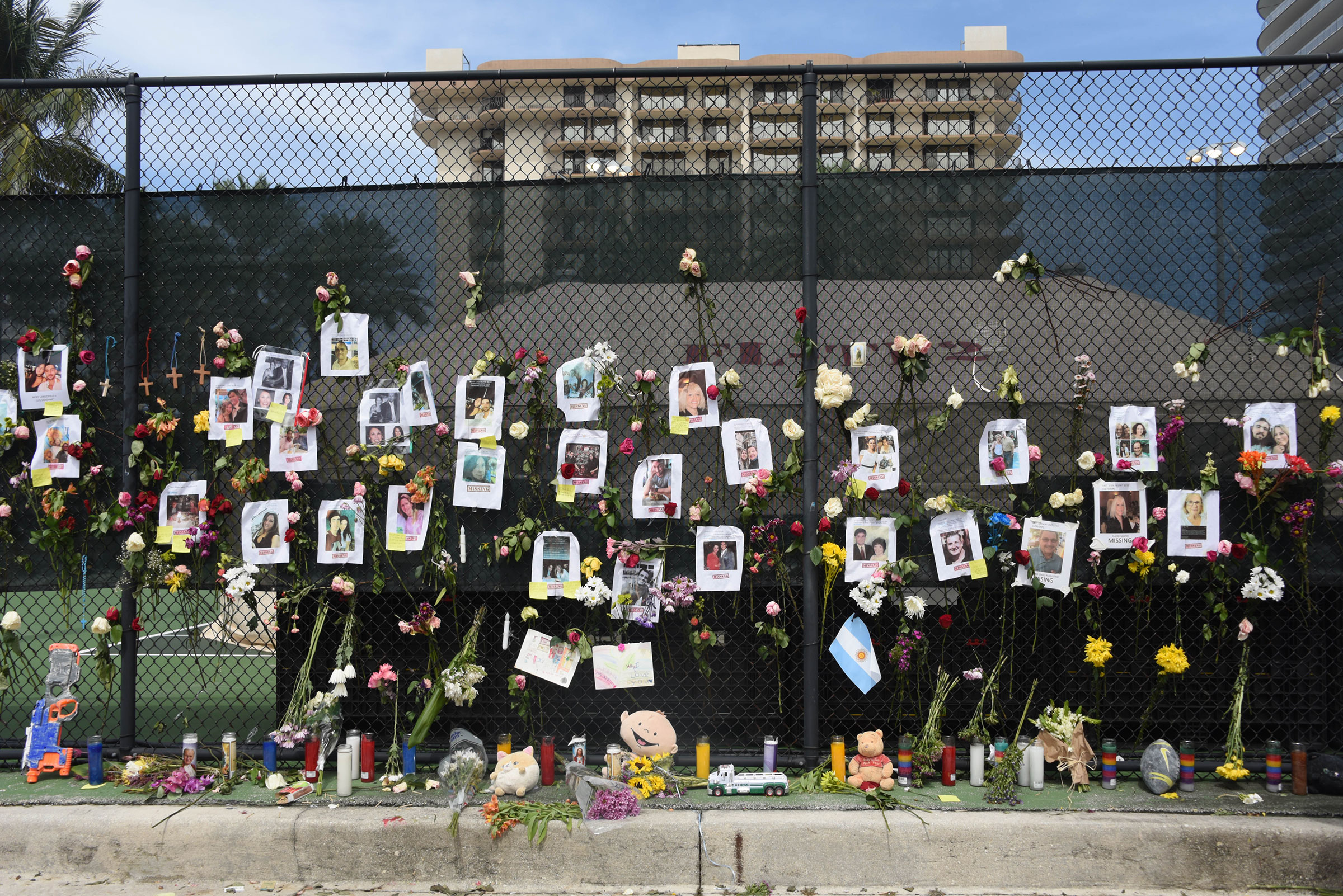 Posters of missing loved ones hang on a fence on a nearby tennis court in Surfside on June 26.