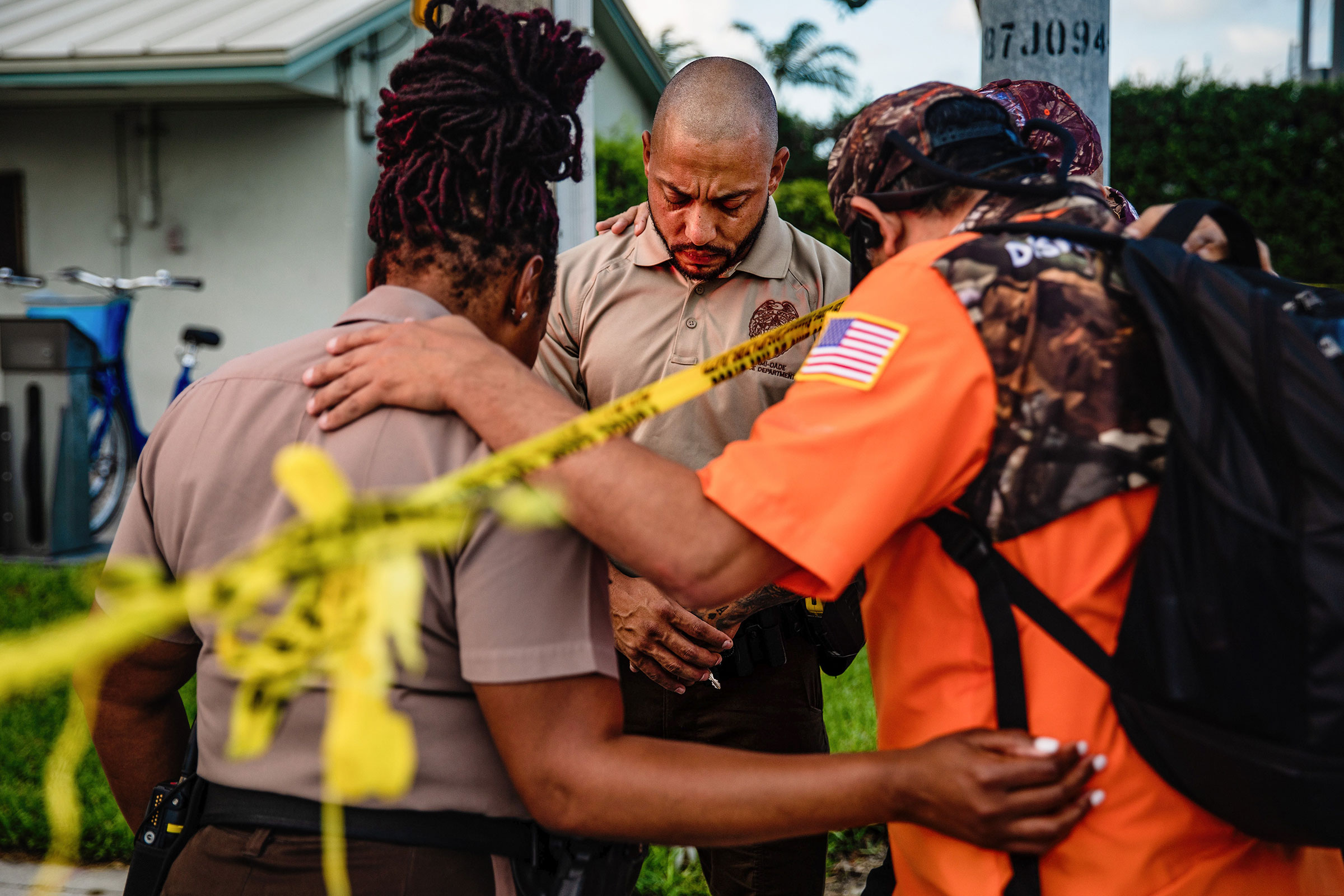 Members of a Christian mens group pray with Miami-Dade Police Department officers outside the Champlain Towers South collapse site on June 26.