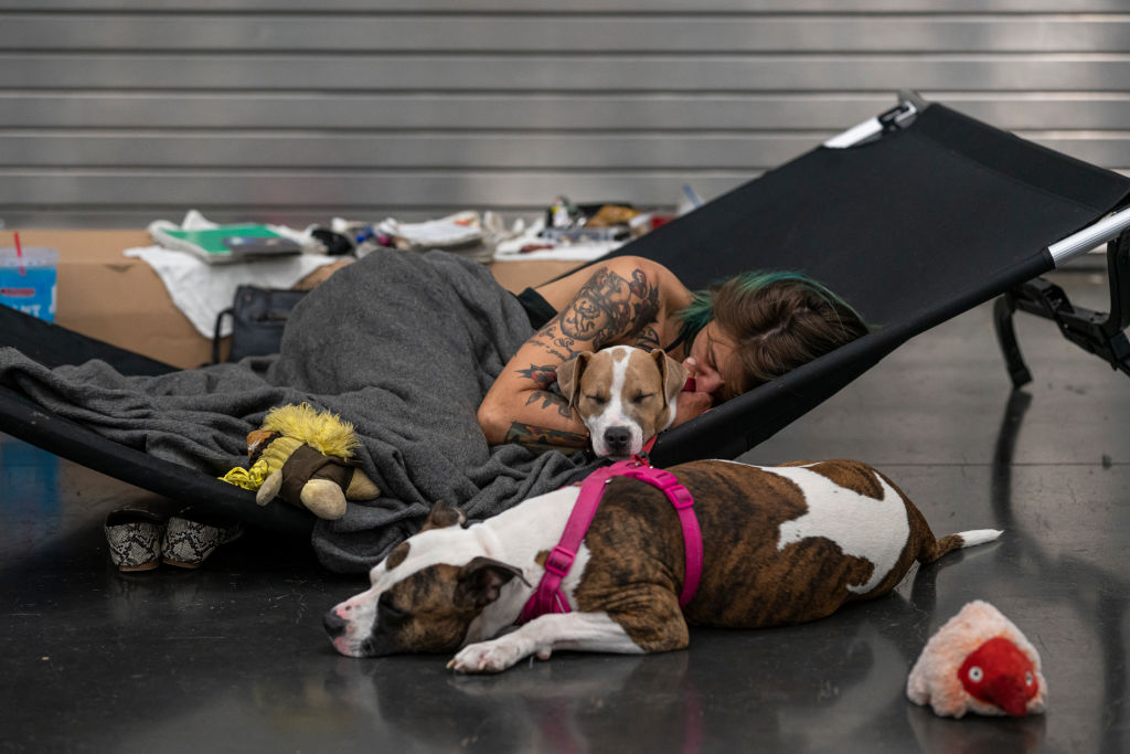 Austun Wilde rests with her two dogs a cooling center in the Oregon Convention Center in Portland, on June 27, 2021.