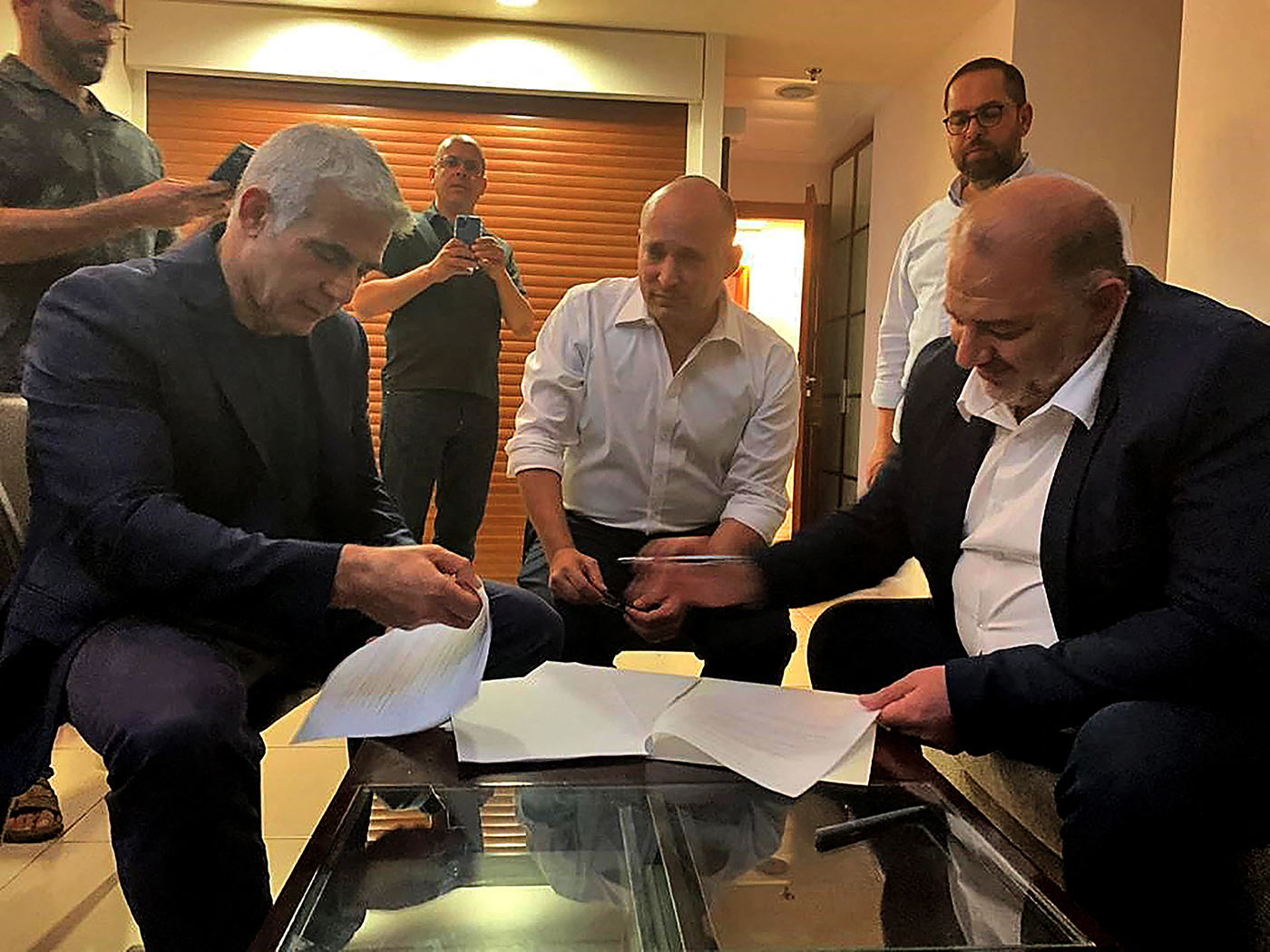 A handout picture provided by the United Arab List on June 2, 2021, shows Mansour Abbas, right, signing a coalition agreement with Israel's opposition leader Yair Lapid, left, and right-wing nationalist Naftali Bennett in Ramat Gan near the coastal city of Tel Aviv.