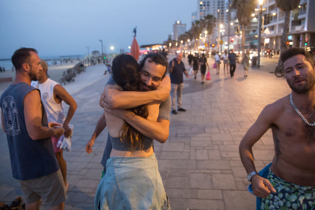 People with no face mask hug as they enjoy time together at the beach in Tel Aviv, Israel on April 19, 2021.