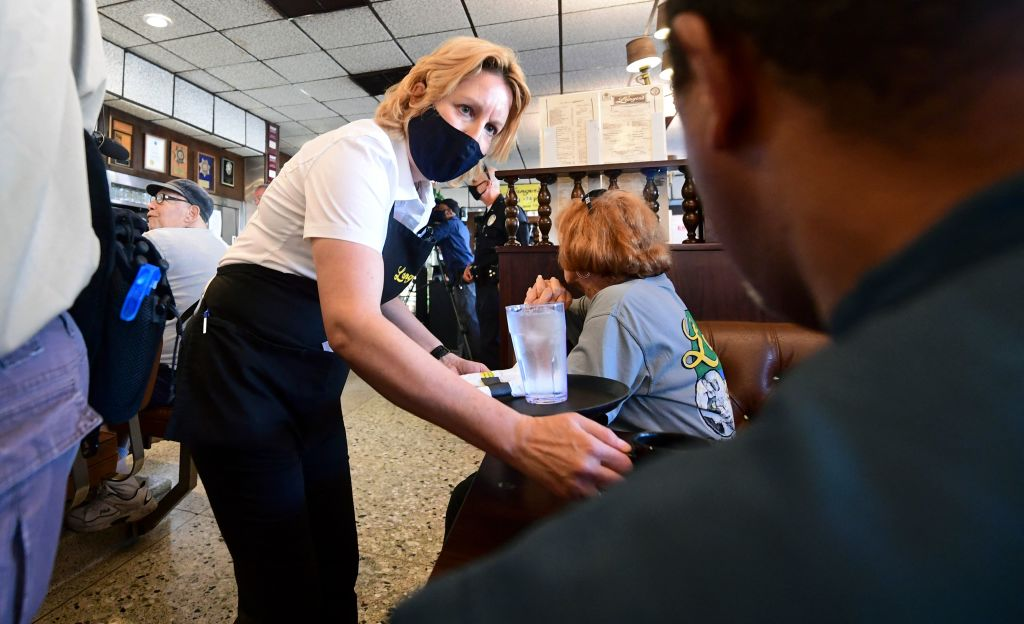 A waitress wears a face mask while serving at Langer's Delicatessen-Restaurant in Los Angeles, California, on June 15, 2021.