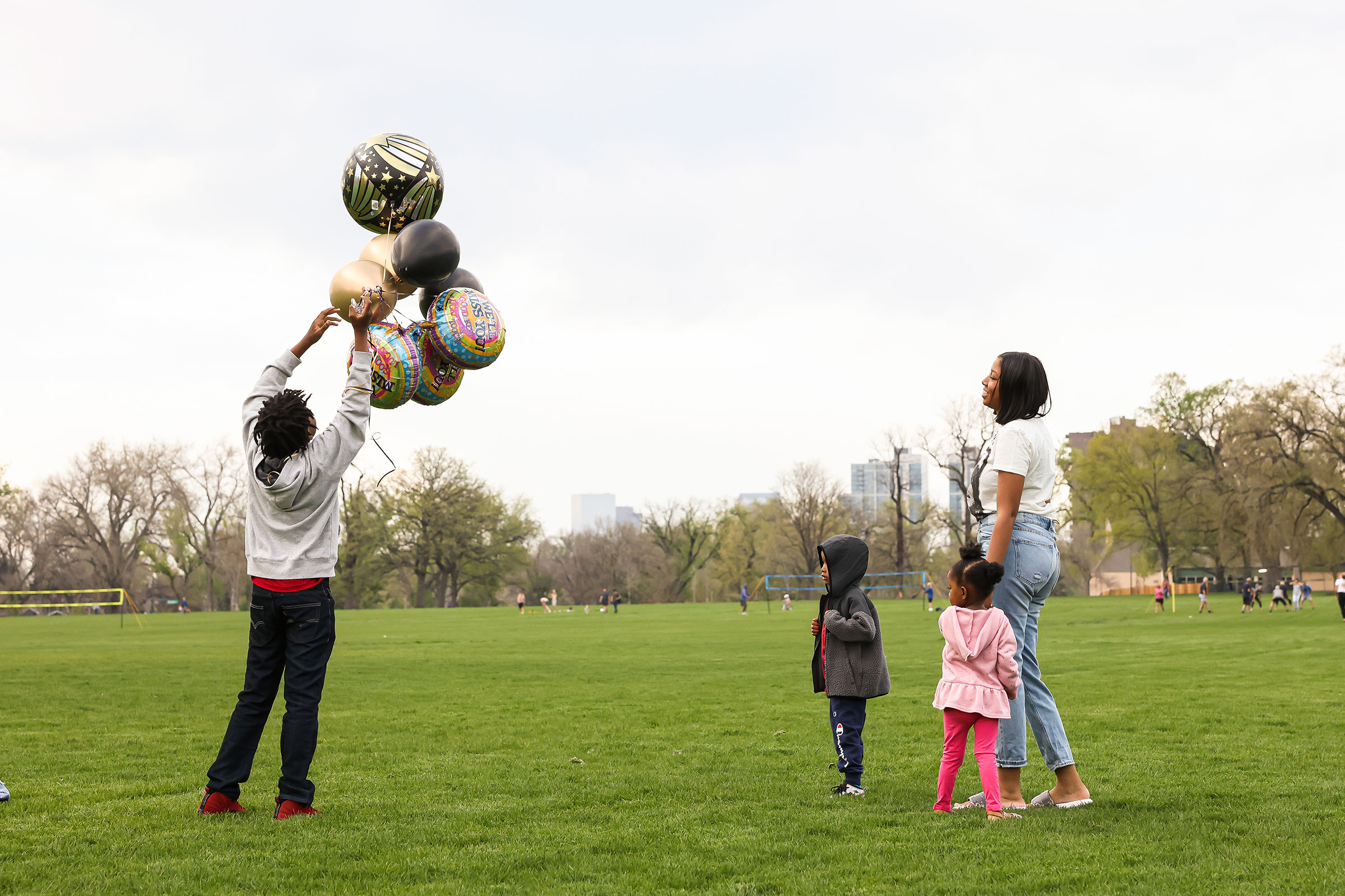 Nehemiah prepares to release balloons in commemoration of his father while his mother Ashley, his 4-year-old bother, Prince, and 3-year-old sister, Zyla, watch nearby