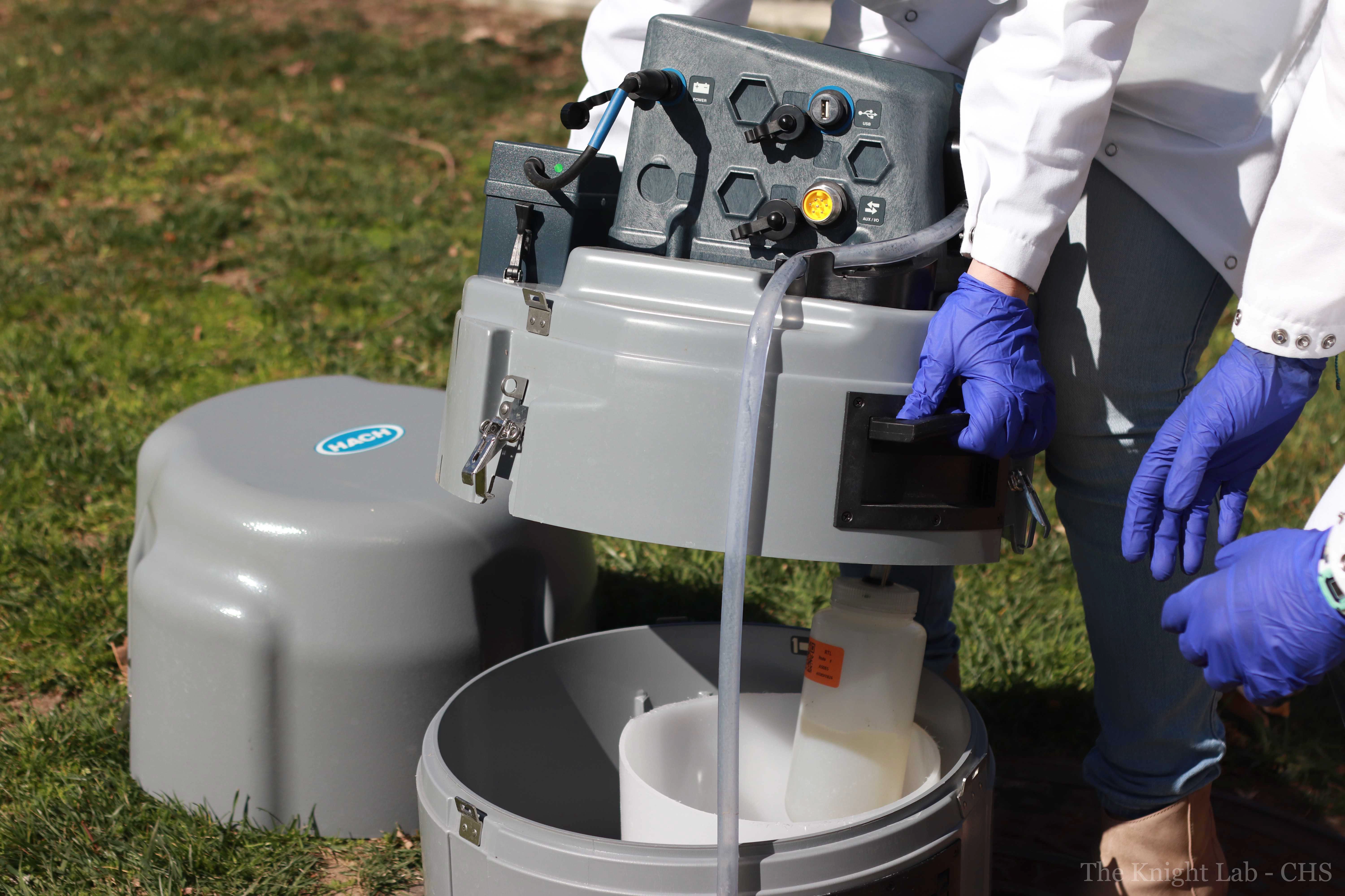 Researchers at UCSD prepare a robot sampler that collects wastewater from the university sewage system.