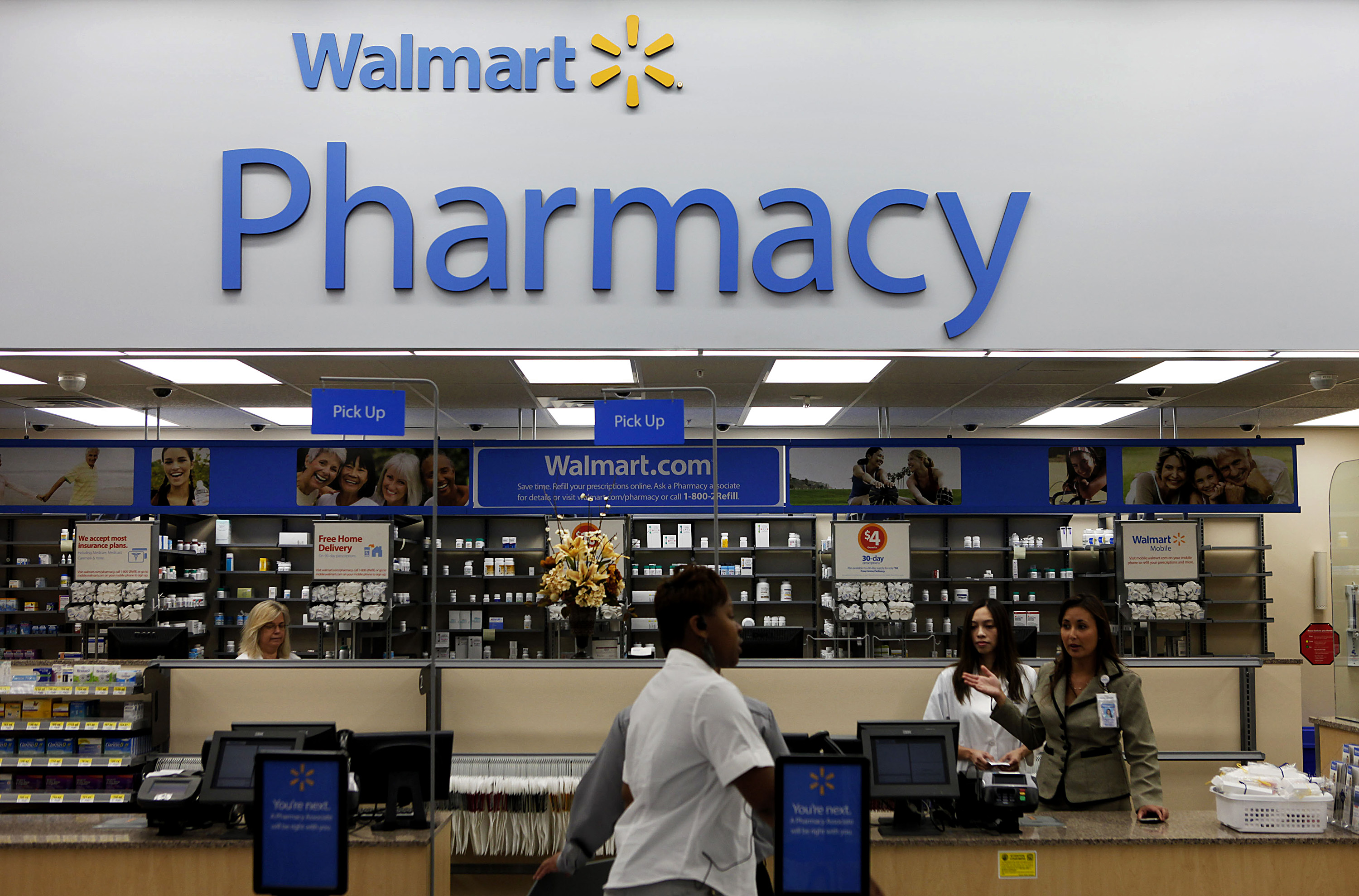 A customer walks past the pharmacy during the grand opening of a new Wal-Mart Stores Inc. location in Torrance, California, U.S., on Sept. 12, 2012.
