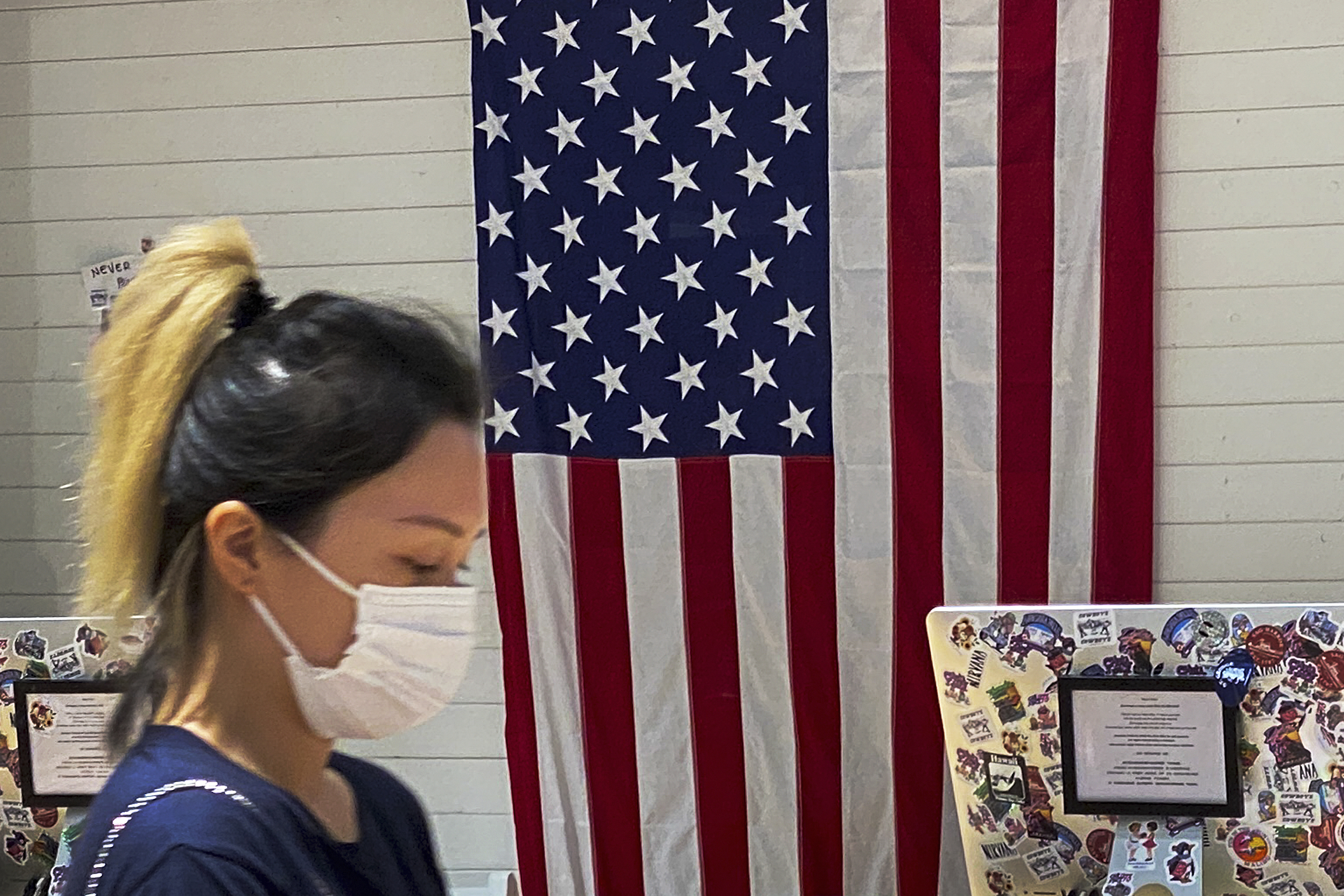 A woman wearing a face mask walks by a counter displaying an American flag at a fashion boutique in Beijing, Sunday, July 11, 2021.
