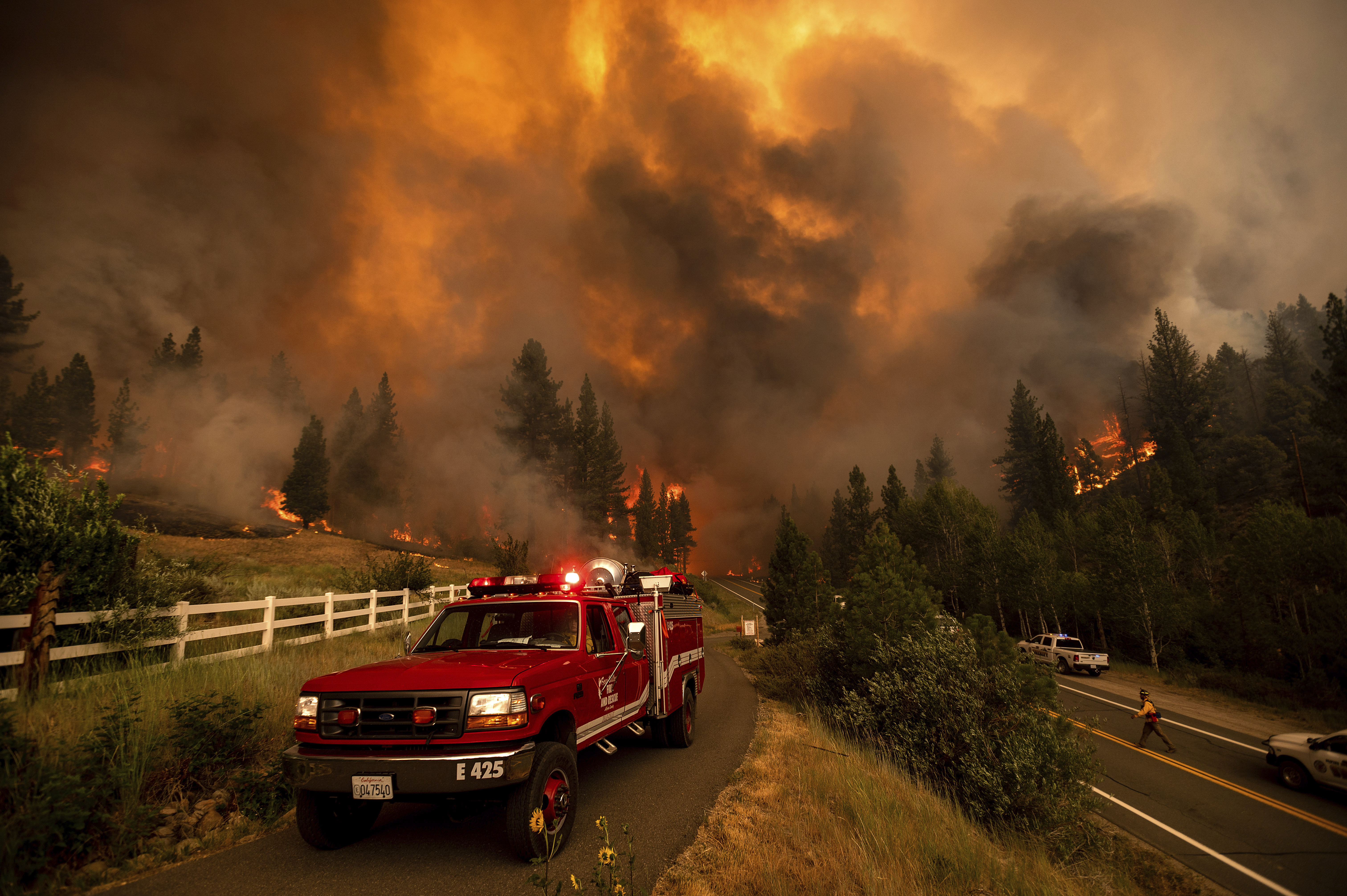 Firefighters battle the Tamarack Fire in the Markleeville community of Alpine County, Calif., on Saturday, July 17, 2021.
