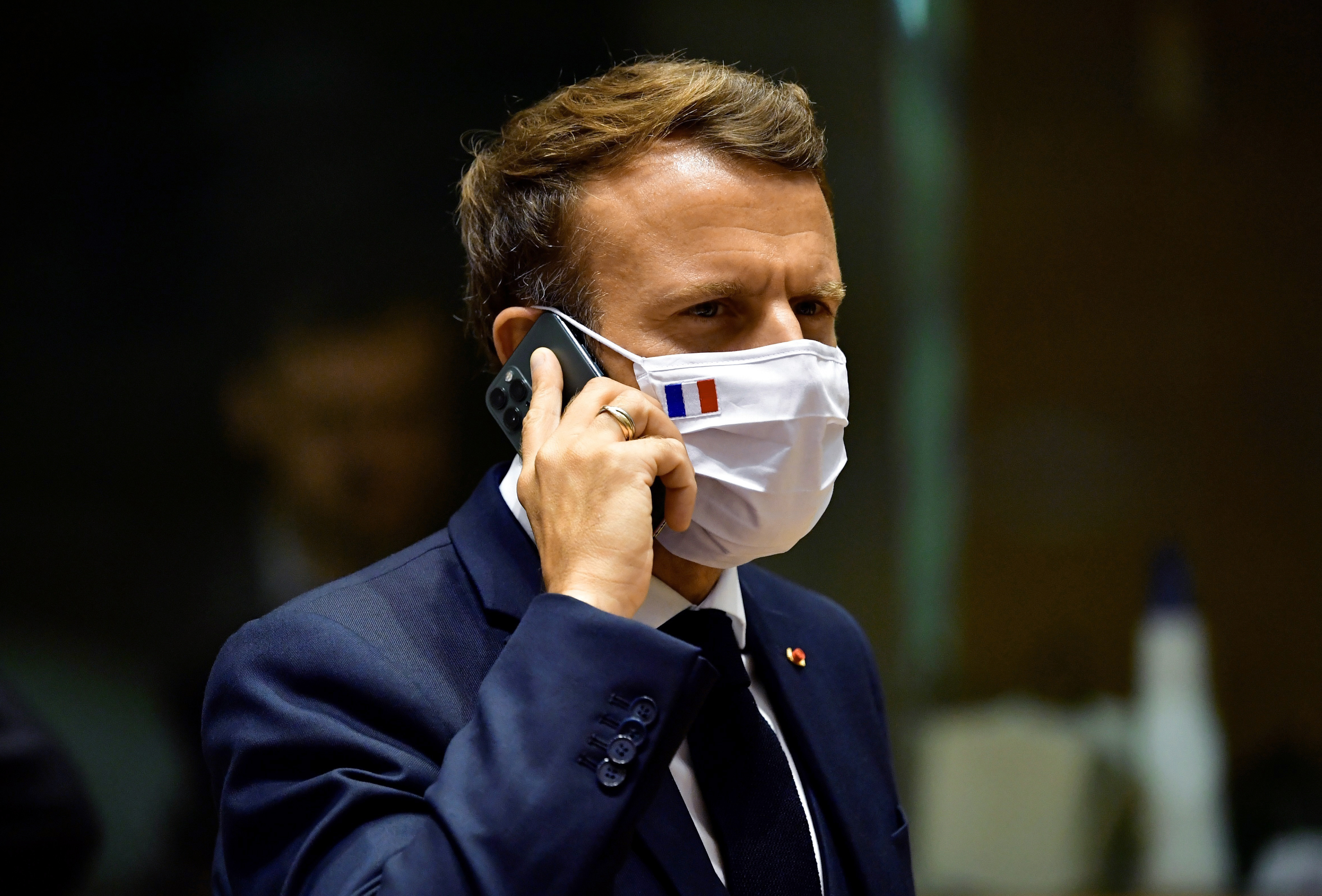 French President Emmanuel Macron speaks on his mobile phone during a round table meeting at an EU summit in Brussels on July 20, 2020.