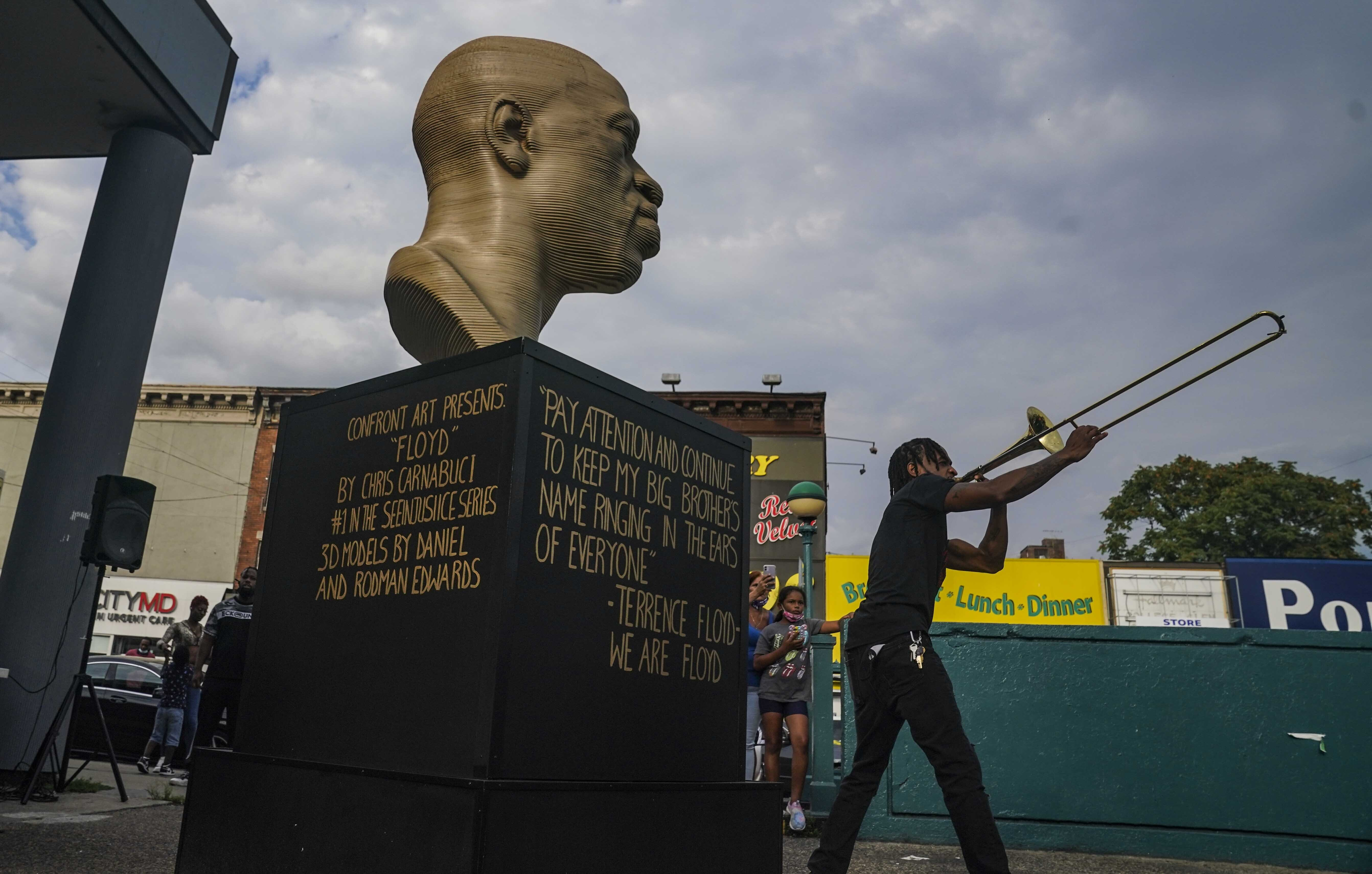 Jonte  Jonoel  Lancaster plays trombone during a celebration for the refurbished George Floyd statue, after it was vandalized following its Juneteenth installation in the Flatbush section of Brooklyn borough of New York, on July 22, 2021.