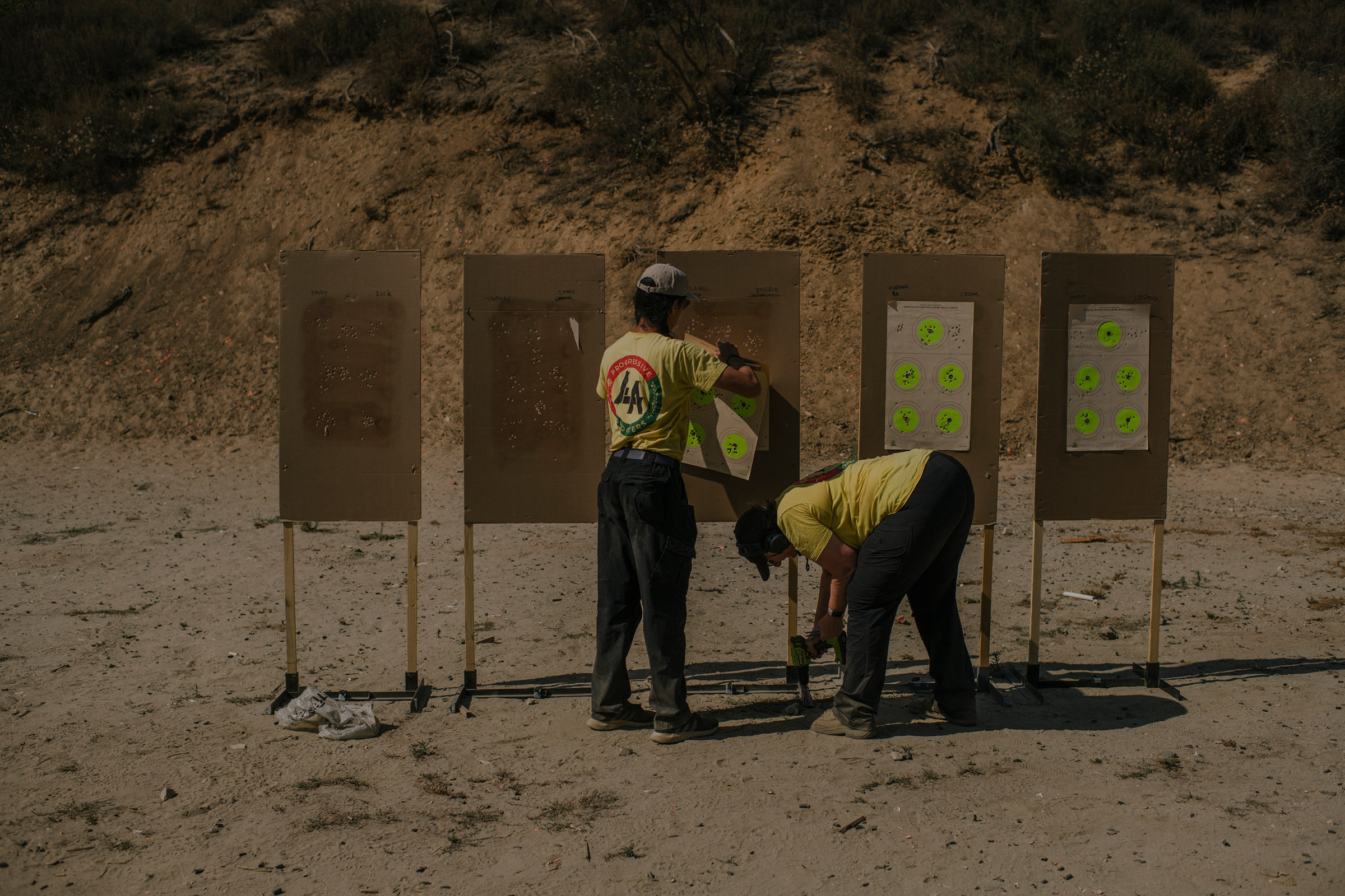 Tom Nguyen and Robbie Tarnove of L.A. Progressive Shooters, a group that works to empower BIPOC gun owners, remove targets after a beginner's class at Burro Canyon Shooting Park in Azusa, CA.