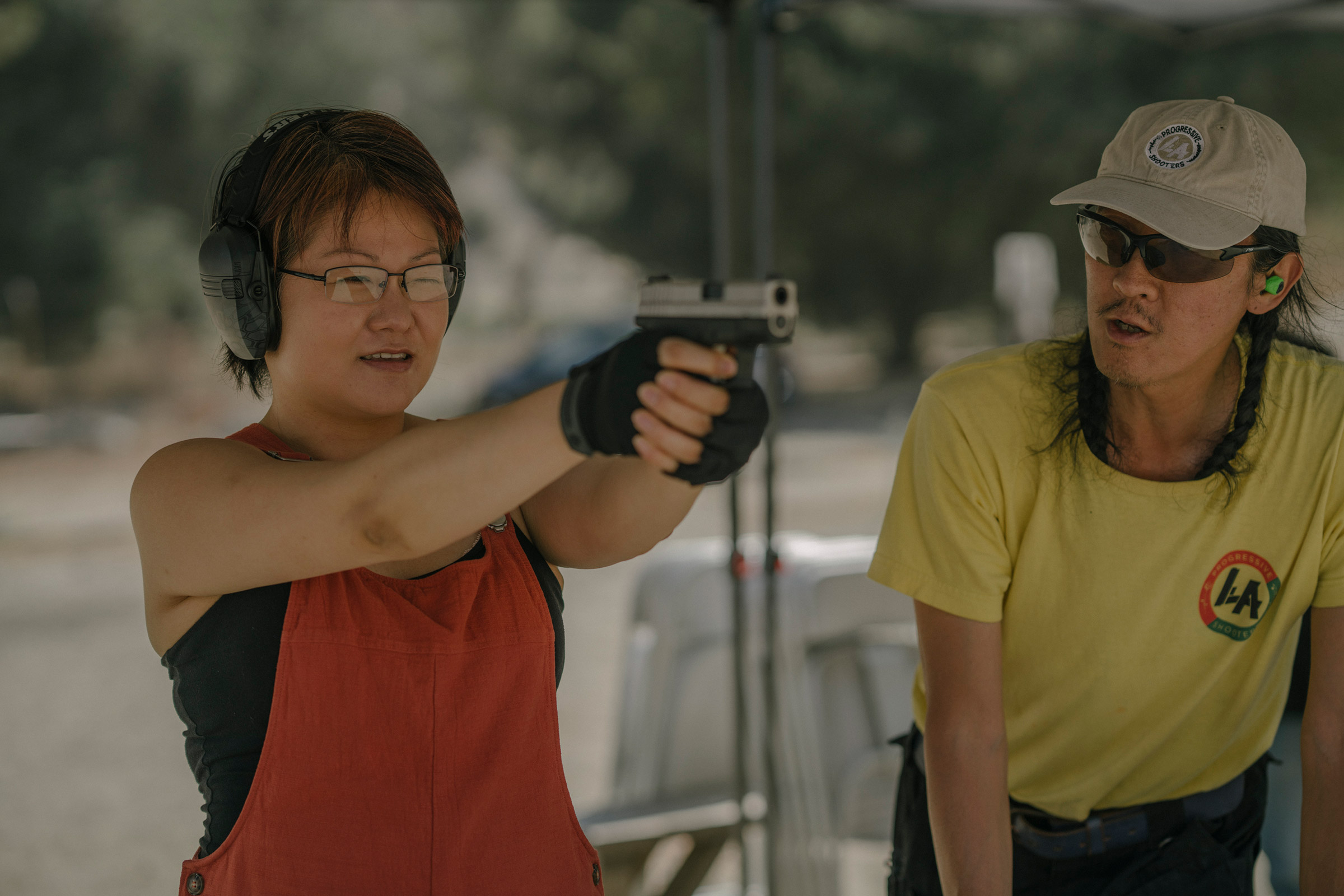 Svetlana Kim practices shooting her new handgun while standing next to Tom Nguyen, instructor and founder of L.A. Progressive Shooters, at the Burro Canyon Shooting Park in Azusa, CA on July 18, 2020.  Nguyen founded L.A. Progressive Shooters in the hopes of diversifying the population of gun owners.