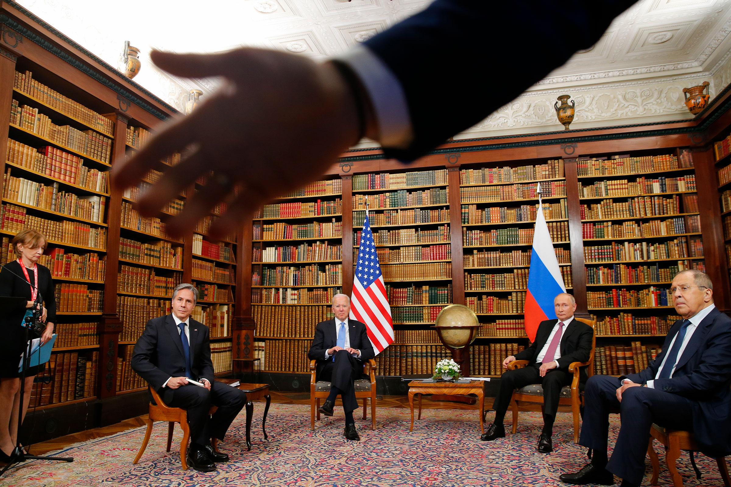 A security officer indicates to the media to step back as U.S. President Joe Biden, second from left, U.S. Secretary of State Antony Blinken, left, Russia's President Vladimir Putin, second from right, and Russia's Foreign Minister Sergei Lavrov, right, meet for the U.S.-Russia summit at Villa La Grange in Geneva, Switzerland, Wednesday, June 16, 2021.