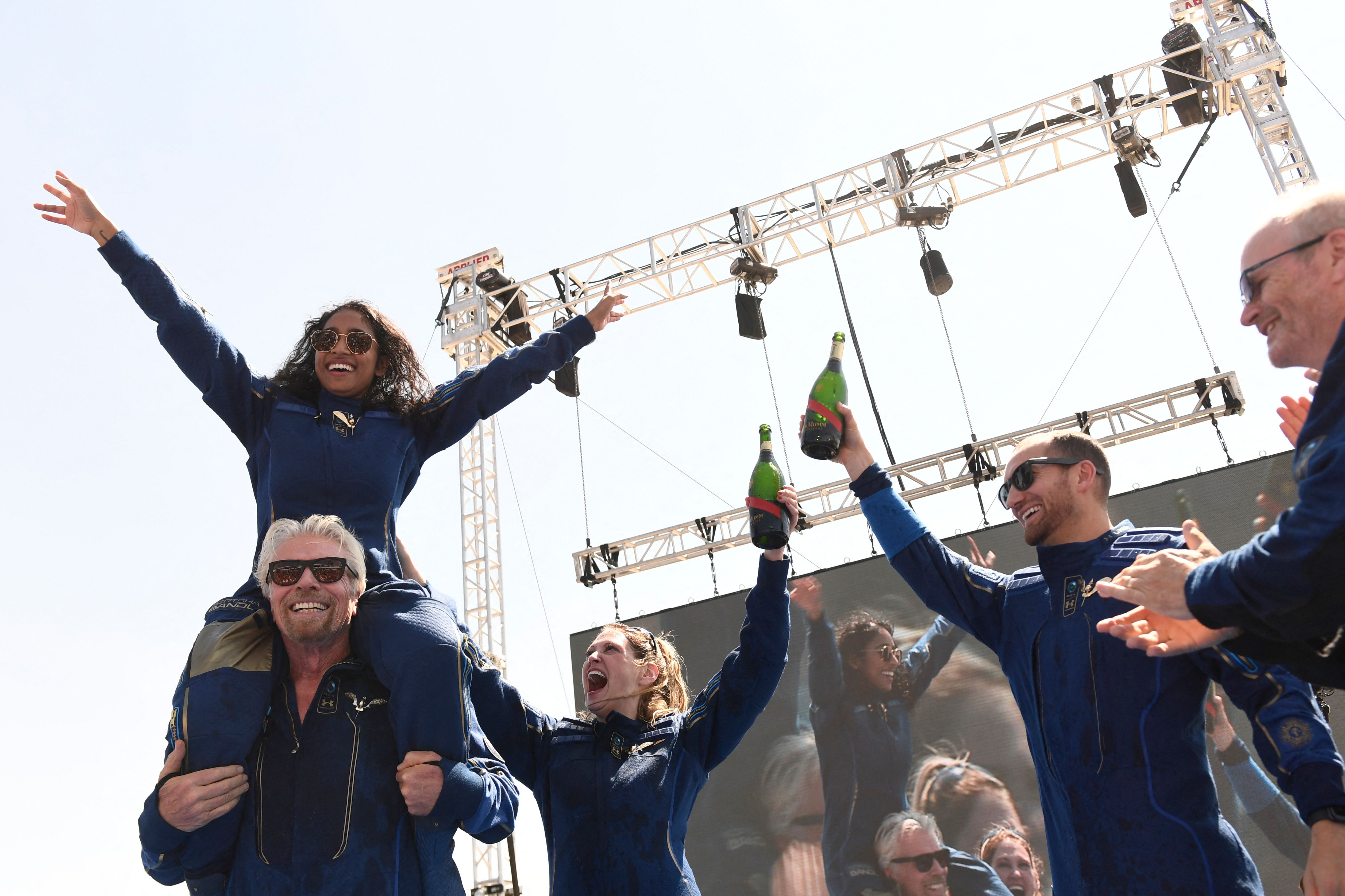 Virgin Galactic founder Sir Richard Branson(L), with Sirisha Bandla on his shoulders, cheers with crew members after flying into space aboard a Virgin Galactic vessel, a voyage he described as the  experience of a lifetime.
