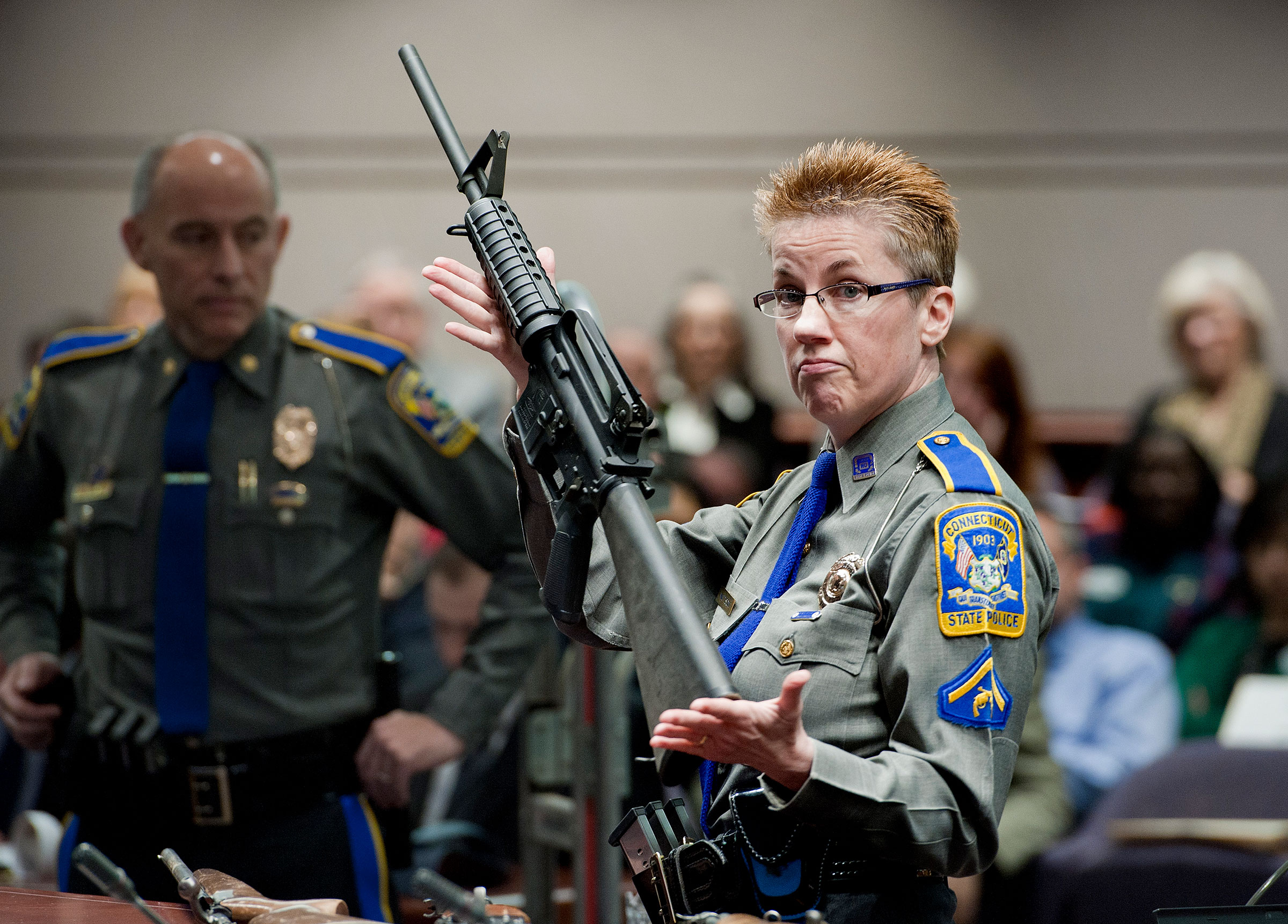 Firearms Training Unit Detective Barbara J. Mattson of the Connecticut State Police holds up a Bushmaster AR-15 rifle, the make and model of gun used in the 2012 Sandy Hook shooting, for a demonstration during a hearing of a legislative subcommittee reviewing gun laws, in Hartford, Conn., on Jan. 28, 2013.