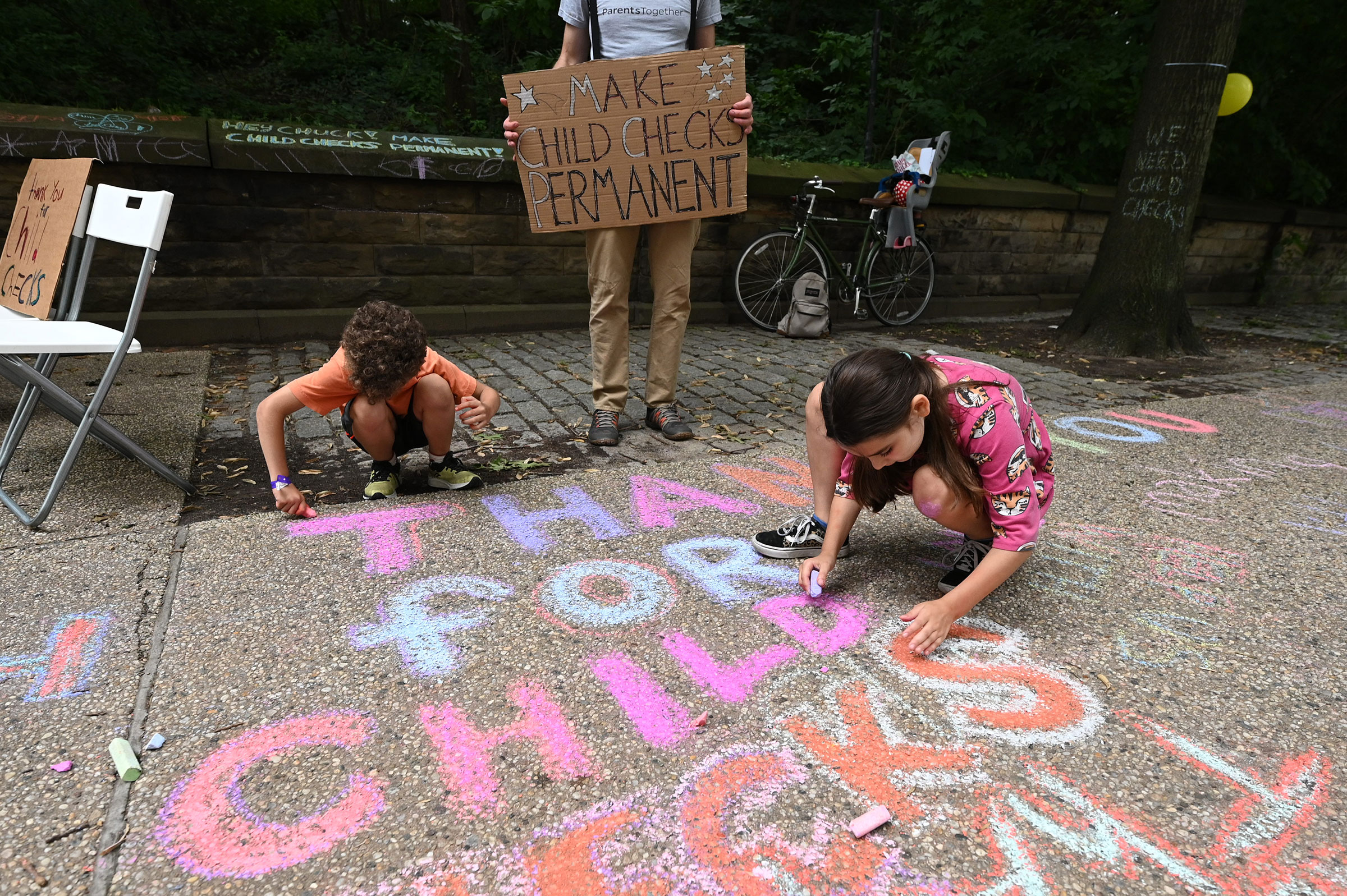 Justin Ruben, Rime Leonard and  Edie Abrams-Pradt draw with chalk to celebrate new monthly Child Tax Credit payments and urge congress to make them permanent outside Senator Schumer's home on July 12, 2021 in Brooklyn, New York.