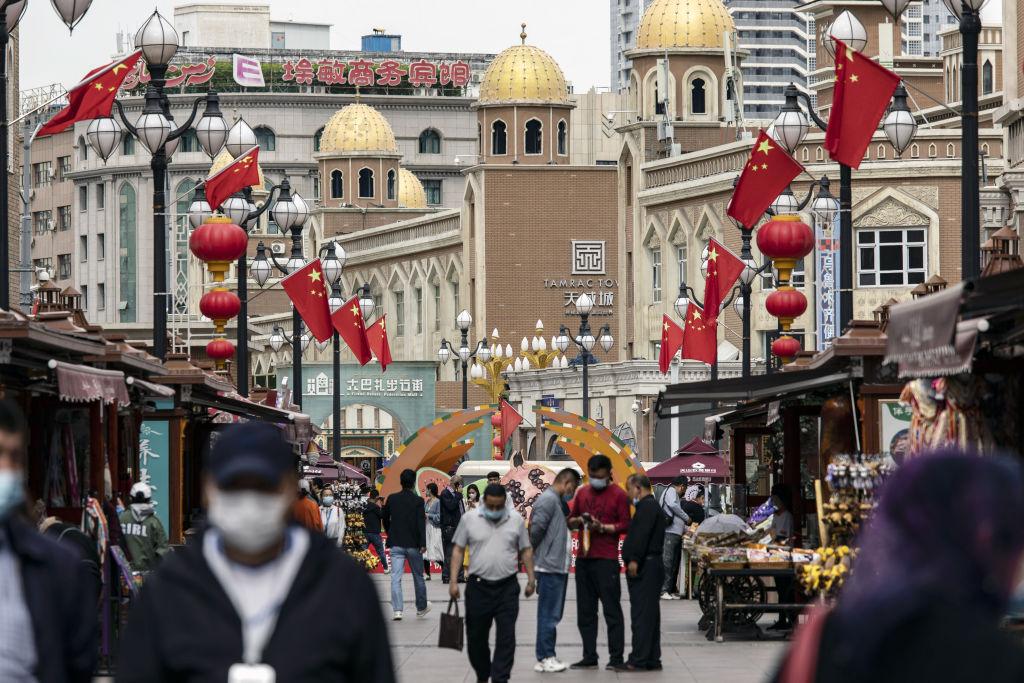 Pedestrians wearing protective masks walk past stalls at the Xinjiang International Grand Bazaar in Urumqi, Xinjiang province, China, on Wednesday, May 12, 2021. China has told nations criticizing its policies inXinjiangto stop interfering in domestic affairs.