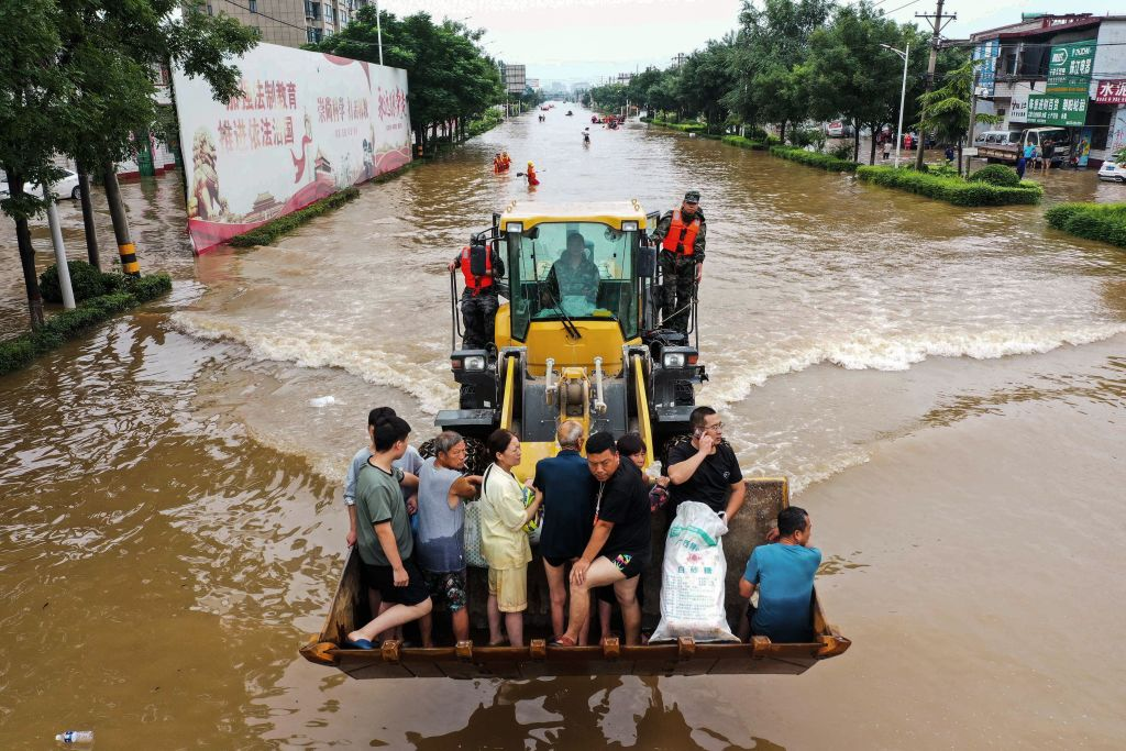 This aerial photo taken on July 23, 2021 shows residents riding in front of a loader to cross a flooded street following heavy rains in Xinxiang, in China's central Henan province.