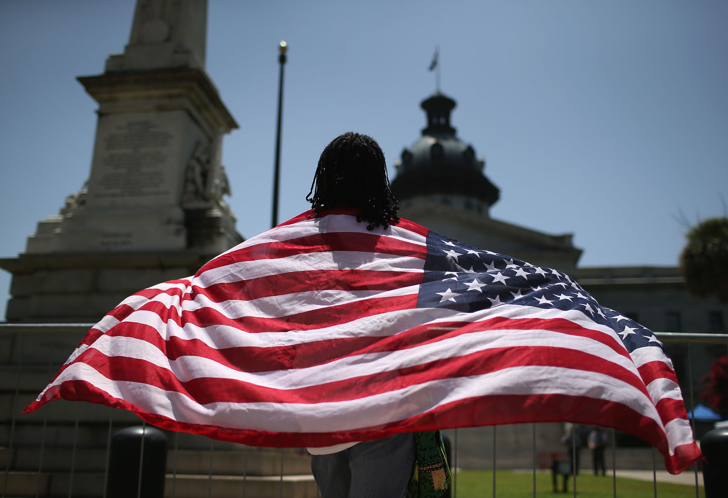 A South Carolinan wears the  Stars and Stripes  after the Confederate  Stars and Bars  were lowered from the flagpole in front of the statehouse on July 10, 2015 in Columbia, South Carolina.