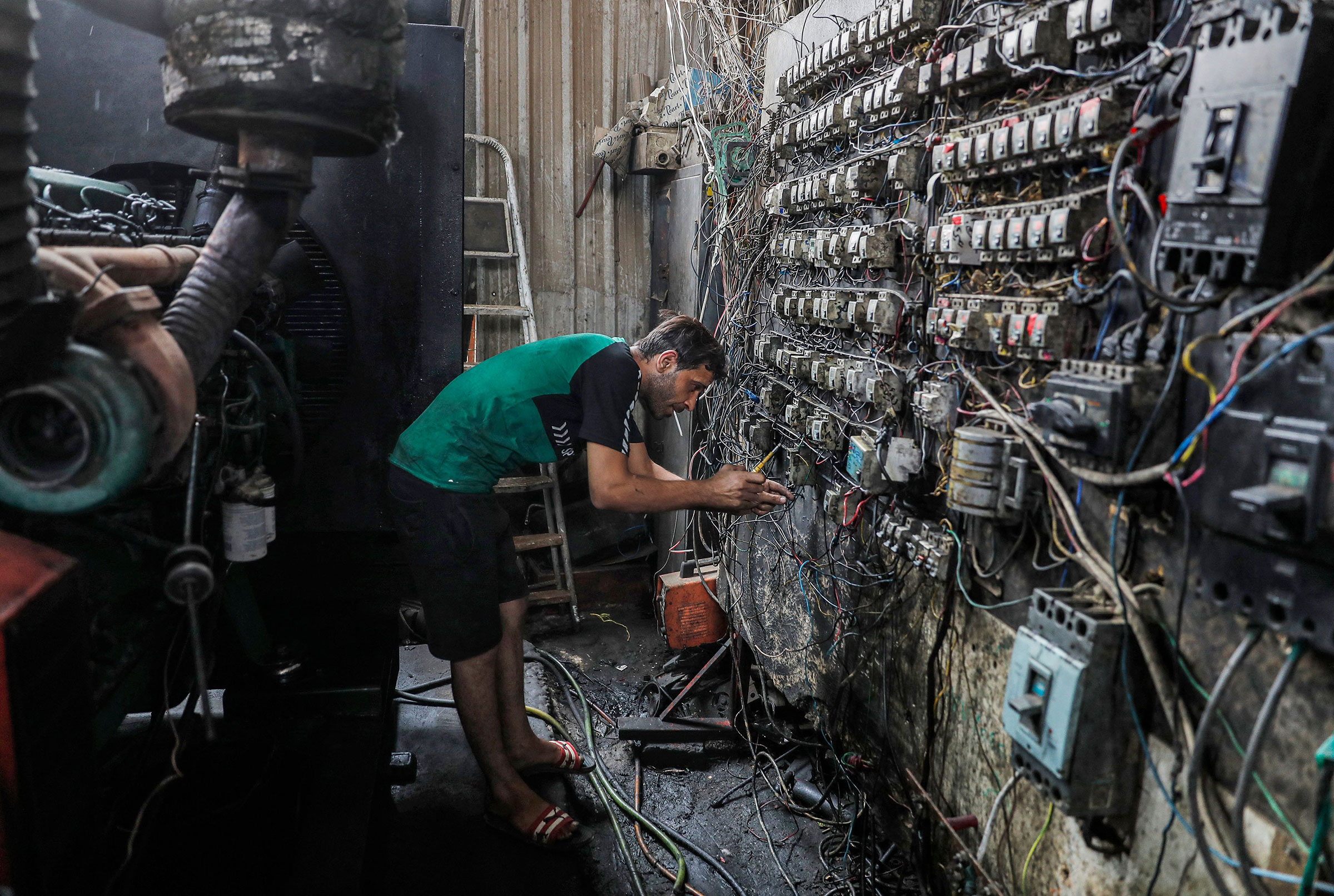A technician controls an electric switch board connecting homes to privately-owned electricity generators in a suburb of Iraq's capital Baghdad on June 30, 2021 as the national electric grid is experiencing outages amidst a severe heat wave.