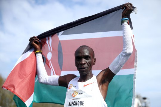 Eliud Kipchoge of Kenya, winner of the gold medal, crosses the finishing line and celebrates with a flag during the NN Mission Marathon held on April 18, 2021 in Enschede, Netherlands.
