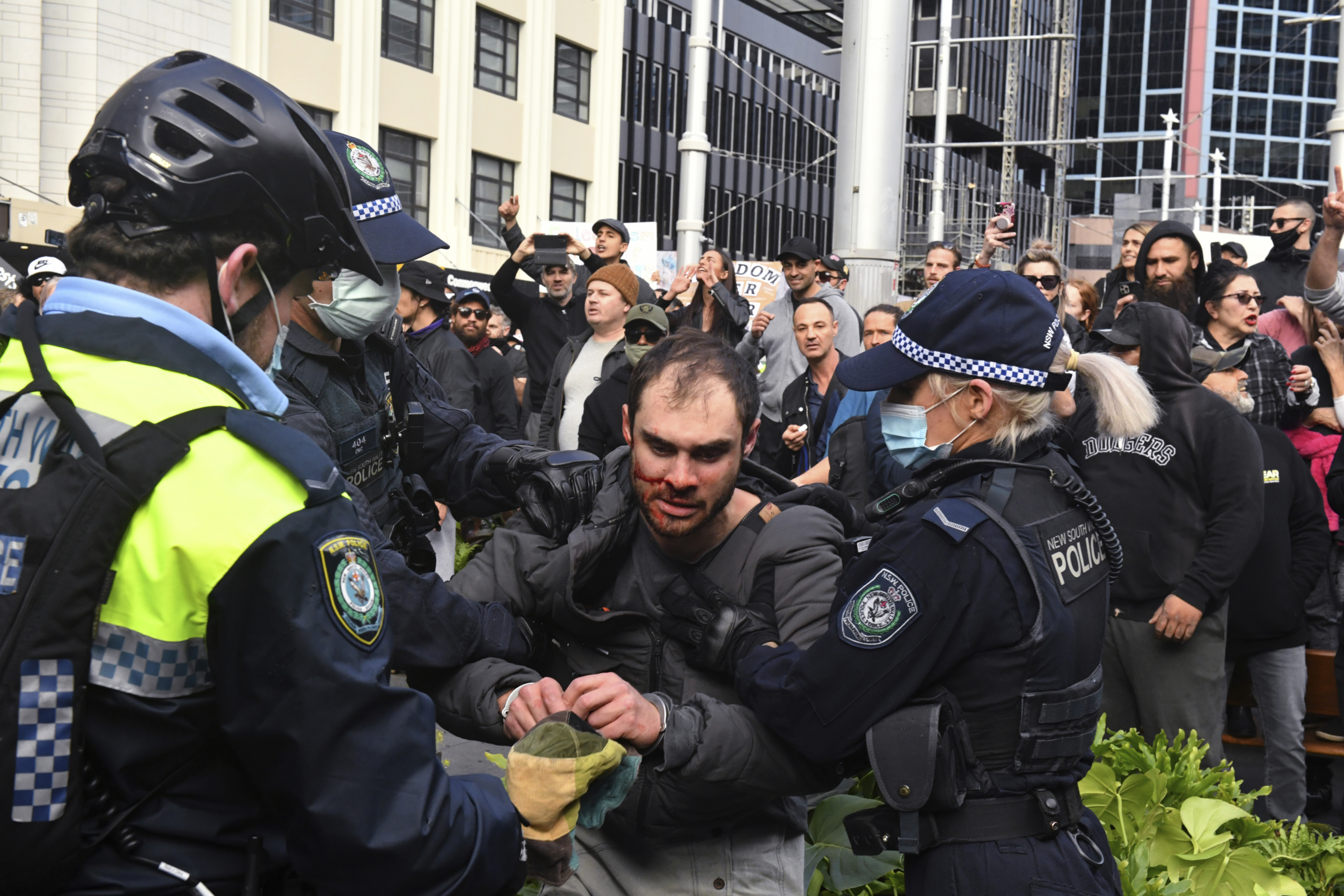 A protester, center, is arrested by police at a demonstration at Sydney Town Hall during a 'World Wide Rally For Freedom' anti-lockdown rally in Sydney, on, July 24, 2021.