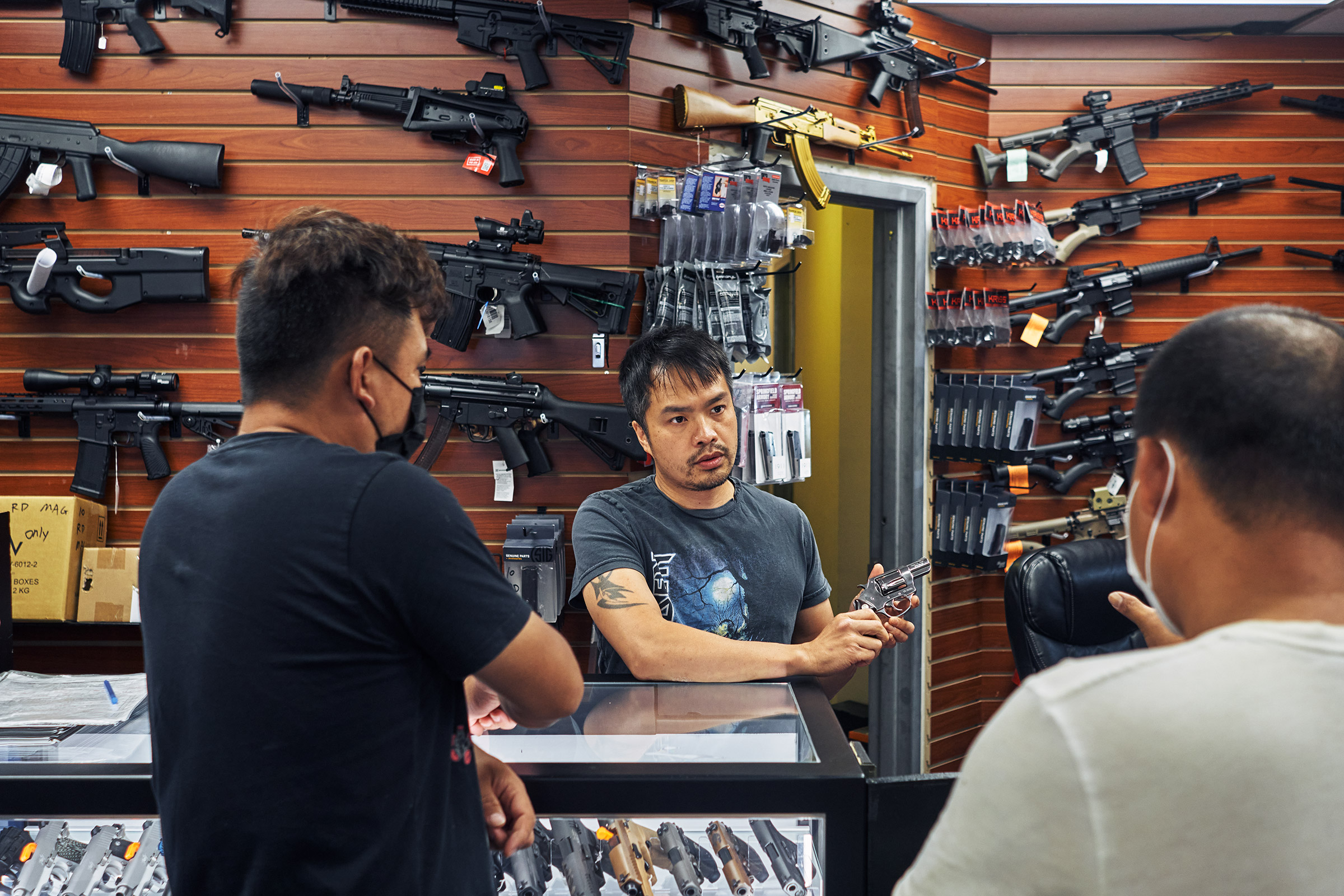 Jimmy Gong, co-owner of Jimmy's Sportshop in Mineola, N.Y., shows a revolver to customers on July 10, 2021.