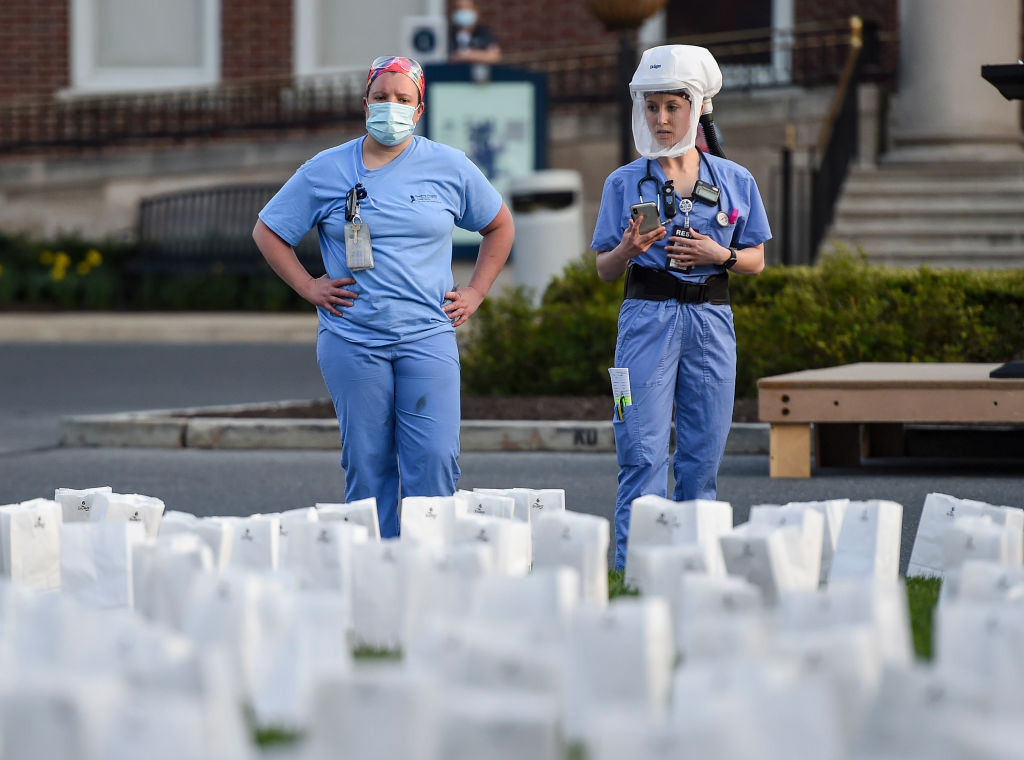 Two healthcare workers in PPE look at the memorial outside the hospital. At the Reading Hospital in West Reading, Penn., Thursday evening April 8, 2021 where the Hospital held a Memorial ceremony for the 938 Berks County Residents who have died from COVID-19. Luminaries were setup for each person who died.