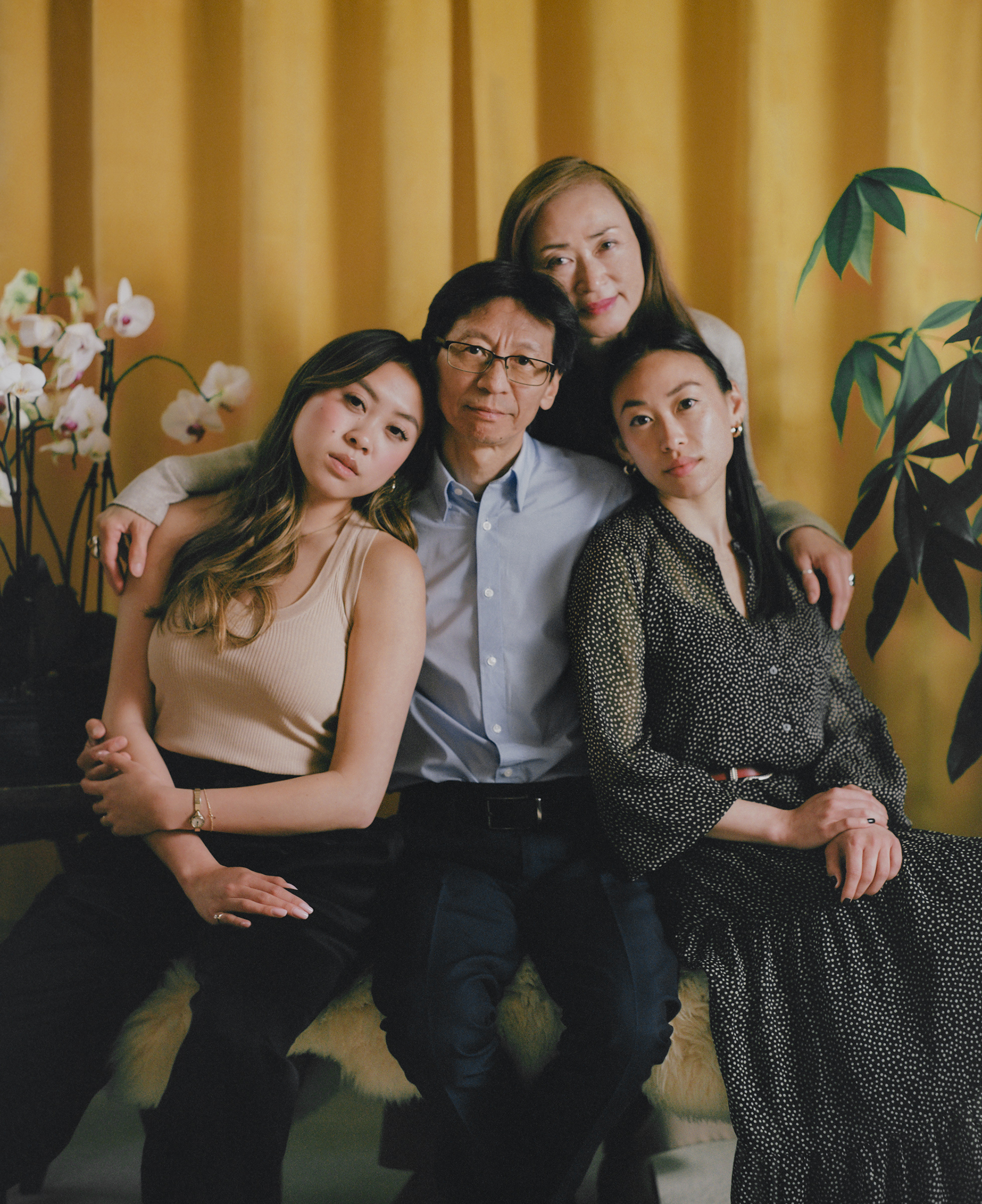 """'HE ISN'T A VICTIM.' Carl Chan, center, sits with his daughters Crystal Chan, right, and Emerald Chan, left, and his wife Eleanore Tang, above, at home in Alameda, Calif., on May 18. As president of the Oakland Chinatown Chamber of Commerce, Carl, 62, has long made the protection of local elders a priority in his work. When attacks against Asian Americans started increasing in 2020, he ramped up his efforts, handing out whistles and air horns to anyone on the street who would take them. """"We respect the elderly,"""" he says. """"To me, to us, to our community, it is the worst when they are attacking our seniors."""" Carl's daughters worried about their father's safety as he spent his time in areas where incidents of violence had taken place. """"What he's doing is so important,"""" Crystal, 28, remembers thinking. """"While there is a risk, we just can't keep thinking about that."""" On April 29, when Carl was on his way to visit an older Asian man who had been assaulted on a bus, he also fell victim to an unprovoked attack. He remembers hearing a man screaming and yelling a racial slur. Then he describes """"a quick punch to my head."""" Crystal said the emotions overwhelmed her quickly; first shock, then anger and sadness. She and her sister, who live across the country in New York, flew home as soon as they could. """"It's not easy for our family, especially [when] the ones close to you become the victim,"""" Eleanore says. """"It's so hard. It's so hard."""" But Carl, scraped and bruised, emerged from the attack even more determined. On May 15, he walked side by side with his daughters and wife in a """"Unity Against Hate"""" rally that he helped organize. """"While he was physically assaulted, he isn't a victim,"""" says Emerald, 24. """"He's showing that he's strong."""""""