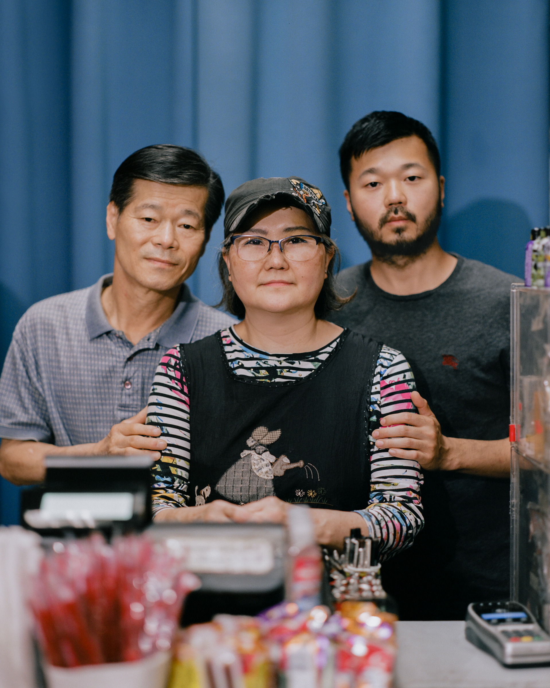 """'I STILL WISH FOR A BETTER LIFE.' Mun Sung, left, and Joyce Sung, center, stand with their 35-year-old son Mark Sung, right, in the family's Charlotte, N.C., convenience store on May 29. The elder Sungs watched helplessly on March 30 as a man smashed through glass with a metal pole, ripped down racks and hurled racial slurs at them inside the store they've owned for two decades. Despite facing racism at work on a daily basis since the pandemic began—even growing hardened to the hatred month after month—Mun never expected his family would fall victim to such violence. """"I feel so terribly bad,"""" the 65-year-old says, """"because how can people do that to us?"""" Less than two months later, it happened again. On May 25, after being told he did not have enough money for cigarettes, a customer shouted racial slurs as he pummeled a sheet of plexiglass at the checkout counter until it shattered on Joyce, 63, bruising her forehead. """"Knowing that we're going to get cursed out every day while we're getting ready for work,"""" she says, pausing to think, """"we don't know what words to use."""" The family has few other options. The pandemic drove down sales at the store by about 45%—and all their employees quit over safety concerns—so the Sungs say they don't have the luxury to stop working. Instead, they clock in 13-hour days, seven days a week, and have developed a routine for responding to hate: call the police, assess the damage, file an insurance claim, then go back to work. It's not the life Mun imagined for himself or his family when he left South Korea for the U.S. in 1983. But he and Joyce keep going, in large part to have some money to leave for Mark's two toddlers, their only grandchildren. """"The first time I came to the United States, I had big dreams and high hopes,"""" Mun says. """"I didn't make it, but I still wish for a better life."""""""