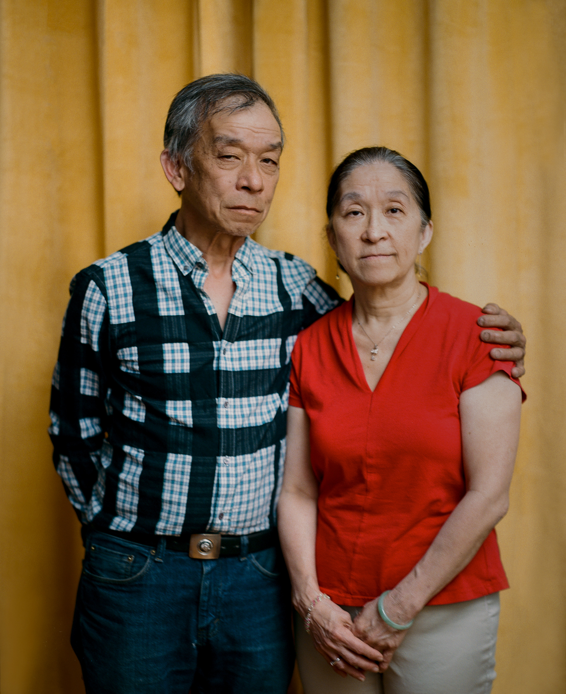 """'I'M PROUD OF WHAT HE DID.' Tommy Lau, 63, stands beside his older sister Maggie Wong inside his Brooklyn home on May 22. On March 23, Lau rushed to protect an elderly Asian couple who were being robbed of their groceries—a choice that Wong says reflects her brother's typical boldness. But when Lau intervened, the man spat on his face, punched him on the side of his head and called him a racial slur. Lau has not been able to return to work as a New York City bus driver, because of neck and shoulder injuries he sustained during the attack. Wong, 66, says it's been difficult to watch her brother continue to struggle months later. """"I feel bad,"""" she says, adding that she supports Lau, emotionally and financially, whenever he needs it. """"I'm proud of what he did."""" Meanwhile, despite all that he's endured, Lau doesn't regret getting involved that day. Since immigrating to the U.S. from Hong Kong at age 3, he has long faced racism—his elementary-school classmates bullied him so often about his birth name, Kok Wah Lau, that his teacher changed it to Tommy—and he has had enough. """"The lowest low of people does that, attacking the elderly,"""" he says. """"I just couldn't take it anymore."""""""