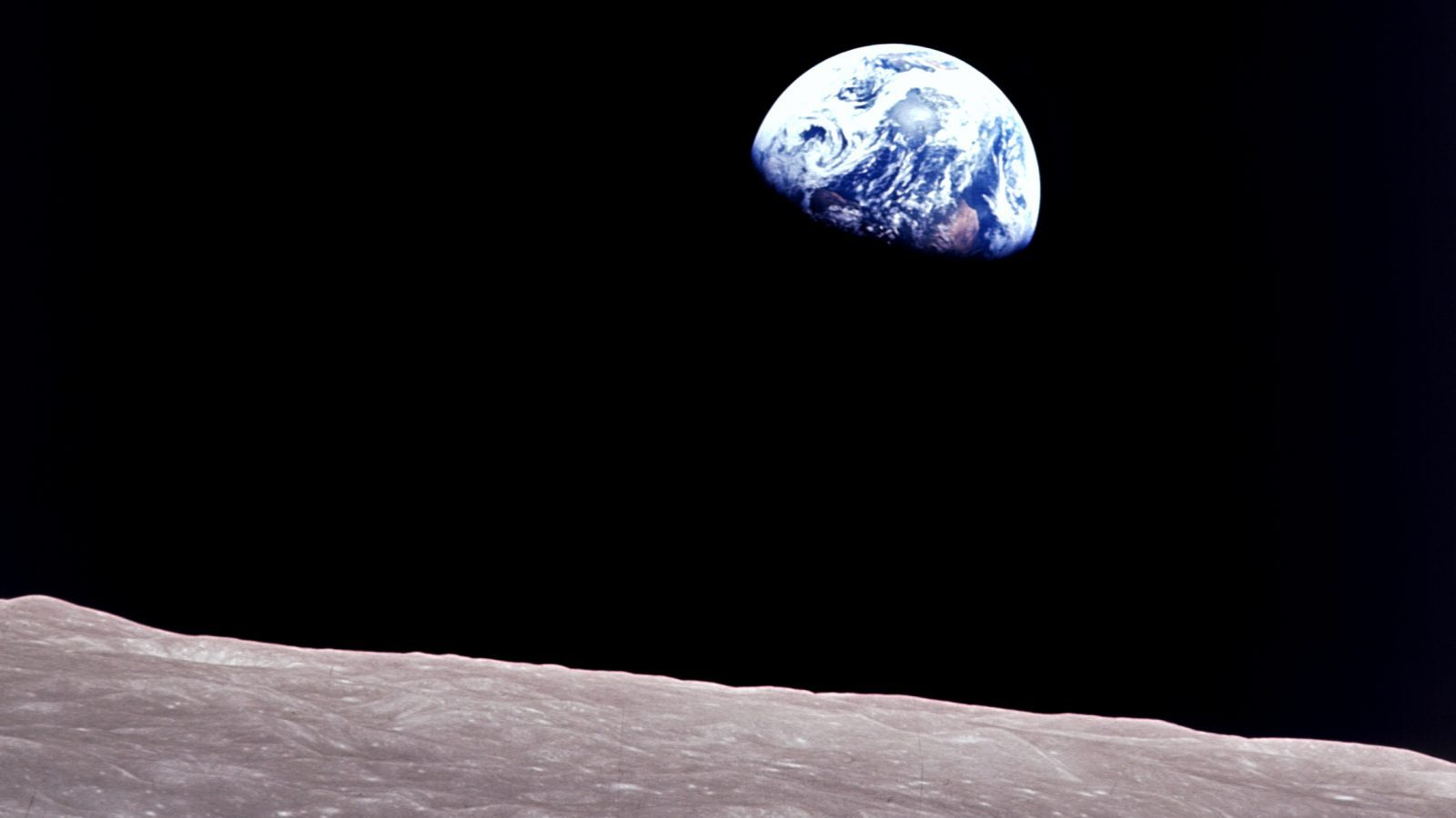 Taken aboard Apollo 8 by Bill Anders, this iconic picture shows Earth peeking out from beyond the lunar surface as the first crewed spacecraft circumnavigated the moon, with astronauts Anders, Frank Borman, and Jim Lovell aboard.