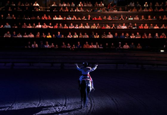 A performer spreads his arms out to those seated in The South as he divides the room of diners at Dolly Parton's Stampede into factions of North and South which will cheer on their teams as they compete in various events like barrel riding, chicken chasing, and pig races in Branson, MO on July 17, 2021.