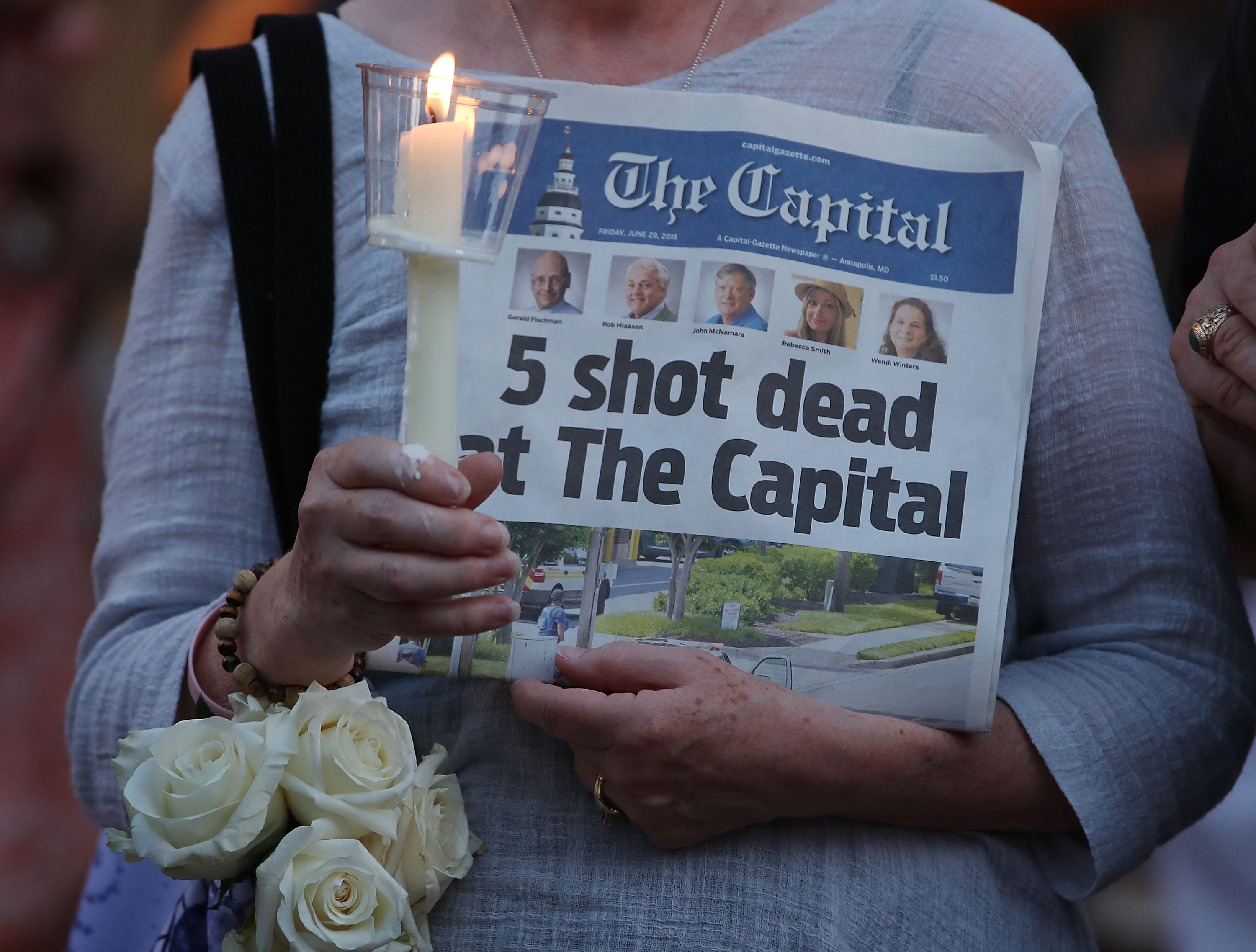 A woman holds the June 29, 2018 edition of the Capital Gazette newspaper during a candlelight vigil to honor the 5 people who were shot and killed at the paper's offices in Annapolis, Maryland a day earlier.