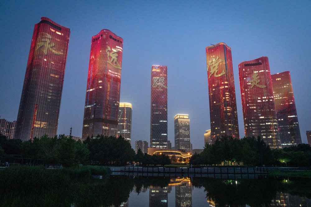 """Chinese characters reading """"Always follow the party"""" illuminate buildings during a light show marking the upcoming centenary of the Community Party in Beijing on June 26, 2021."""