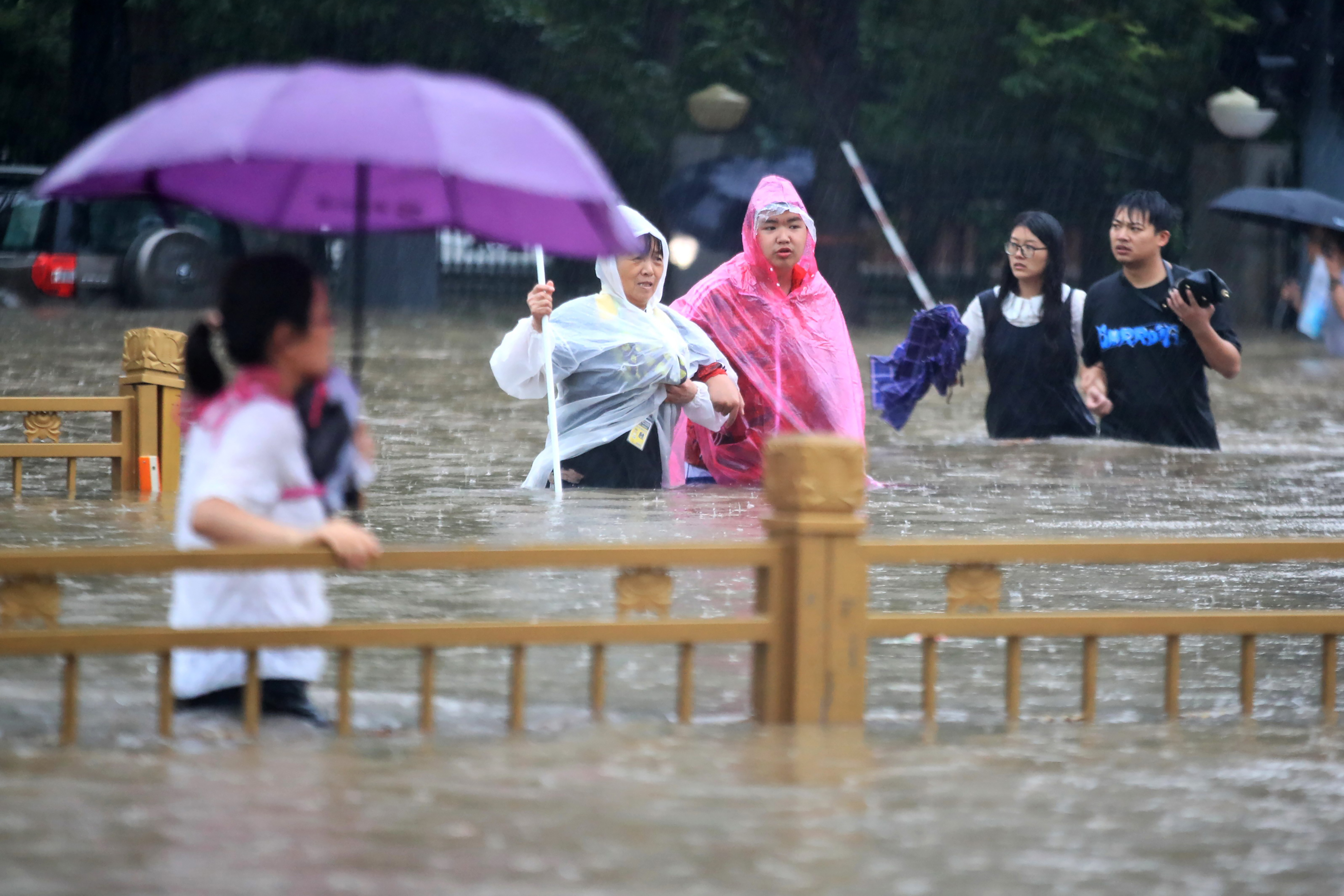 People walk through floodwaters along a street in Zhengzhou in central China's Henan Province, Tuesday, July 20, 2021. China's military has blasted a dam to release floodwaters threatening one of its most heavily populated provinces. The operation late Tuesday night in the city of Luoyang came after several people died in severe flooding in the Henan provincial capital of Zhengzhou, where residents were trapped in the subway system and left stranded at schools, apartments and offices.
