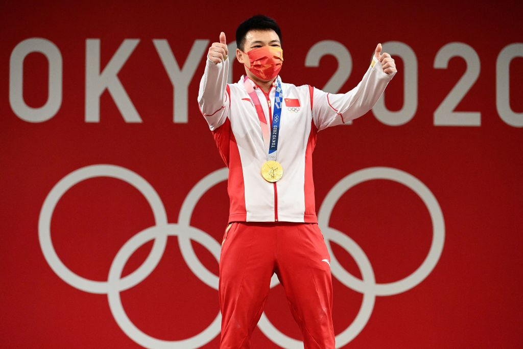 Gold medallist China's Chen Lijun gestures as he stands on the podium for the victory ceremony of the men's 67kg weightlifting competition during the Tokyo 2020 Olympic Games at the Tokyo International Forum in Tokyo on July 25, 2021.