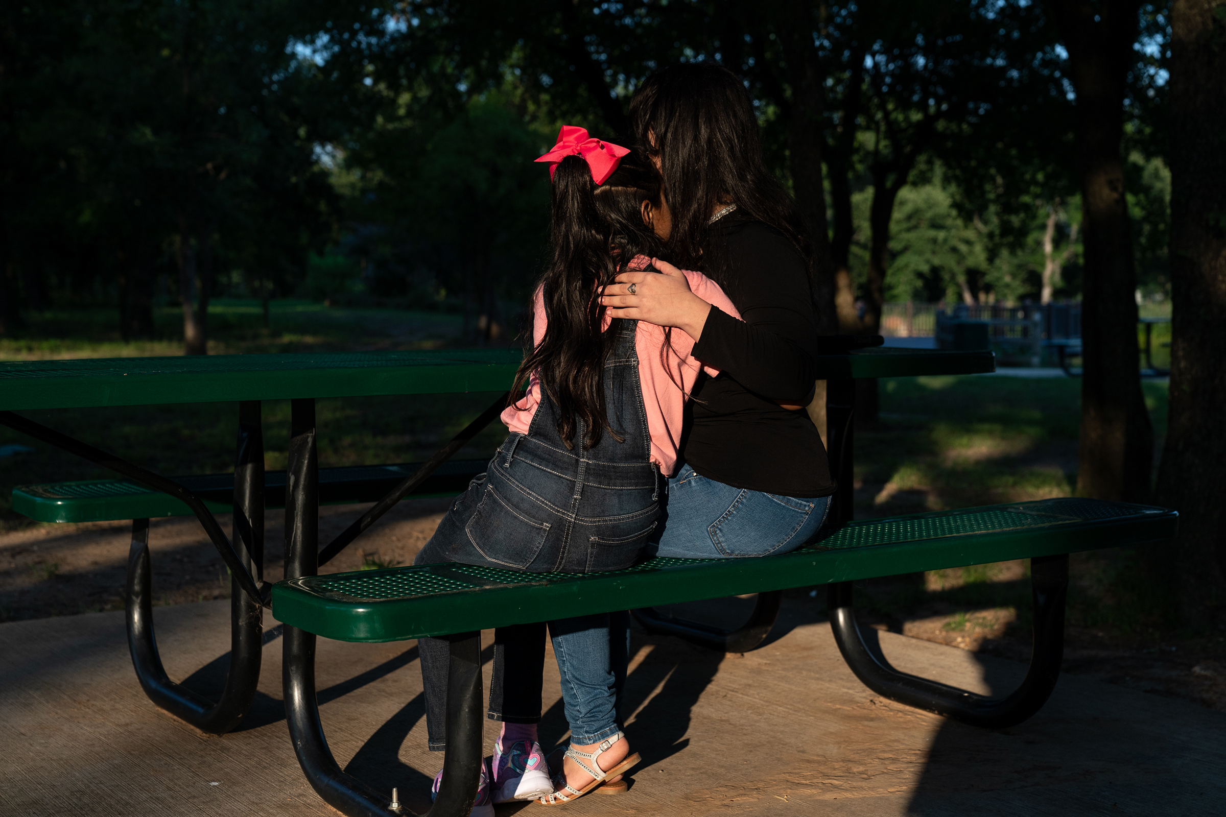 Estefani and her eight-year-old daughter, Ashly, embrace in a park near the home of relatives in June.