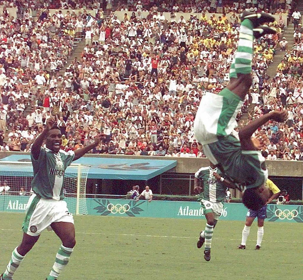 Nigeria's Celestine Babayaro (R) makes a flip after scoring a goal against Brazil during the Olympic soccer semi-final Brazil vs Nigeria in Athens, Ga., on July 31, 1996. Nigeria won 4-3.