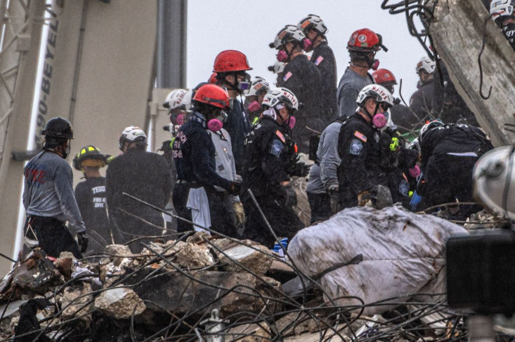 After a brief stop to demolish the standing debris, search and rescue personnel continue to work in the rain on the rubble pile of the 12-story Champlain Towers South condo that partially collapsed on July 5, 2021 in Surfside, Florida.
